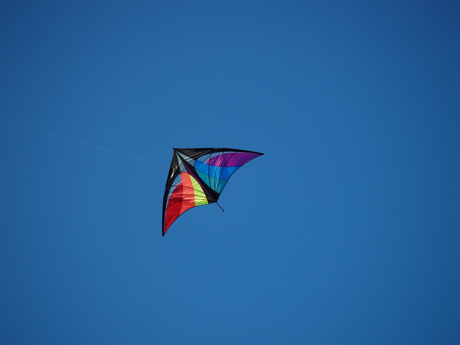 A triangular rainbow kite against a deep blue sky.