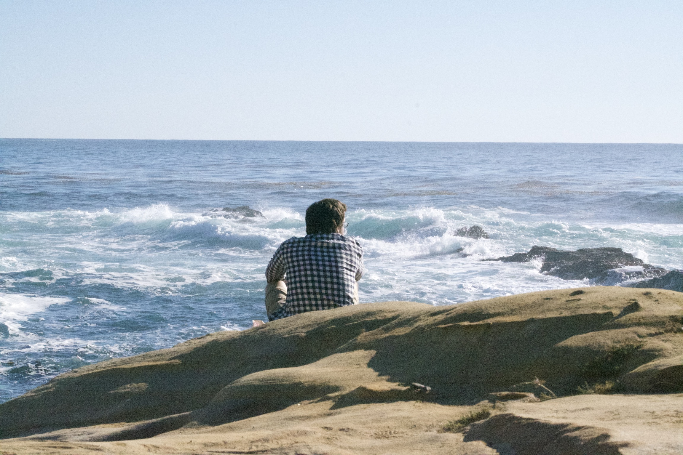 A man sits on rocky ground, looking at the ocean.