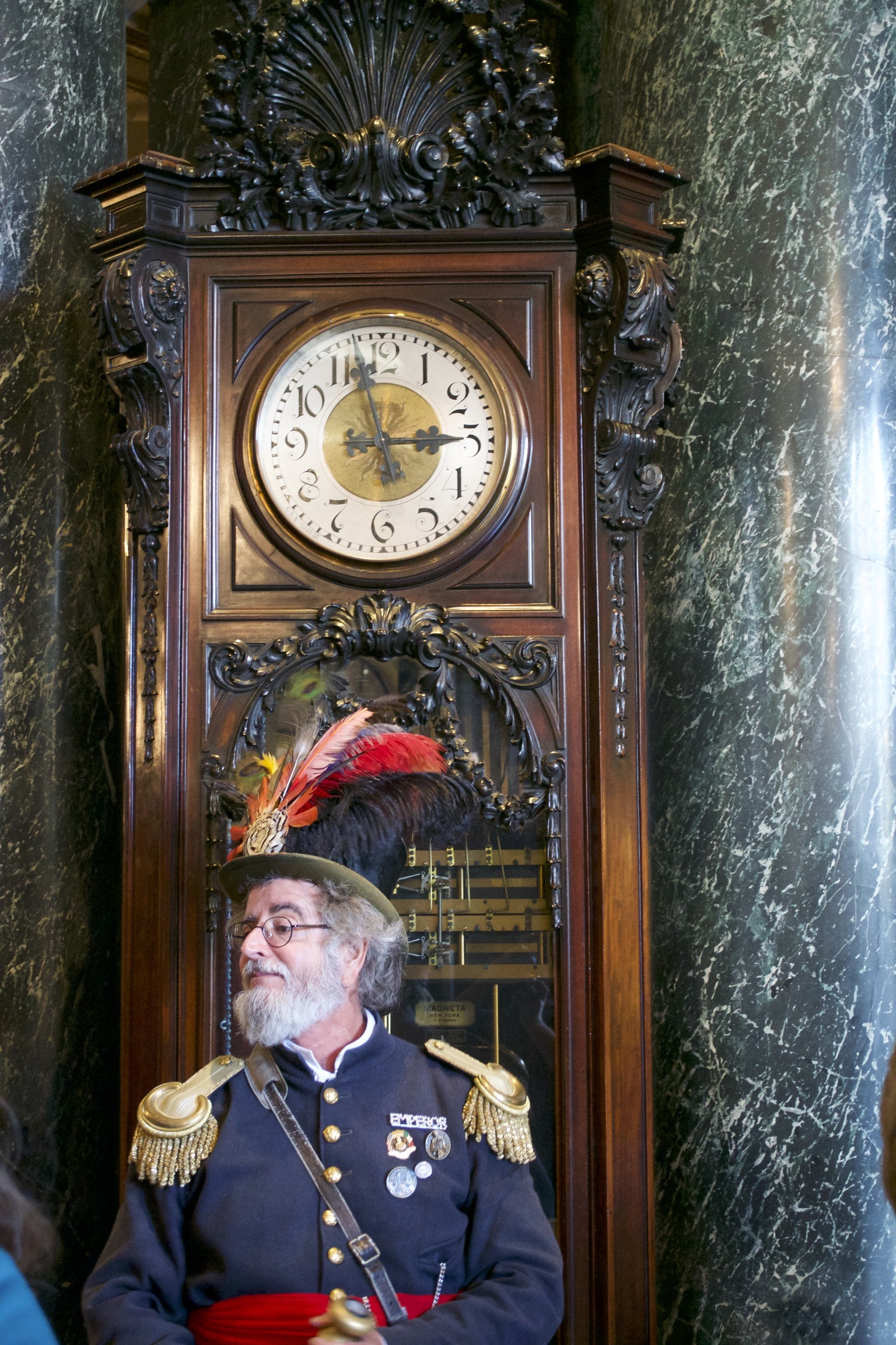 A man in a navy blue officer's jacket with gold epaulets, a red cumberbund, and a feathered top hat stands in front of a huge grandfather clock.