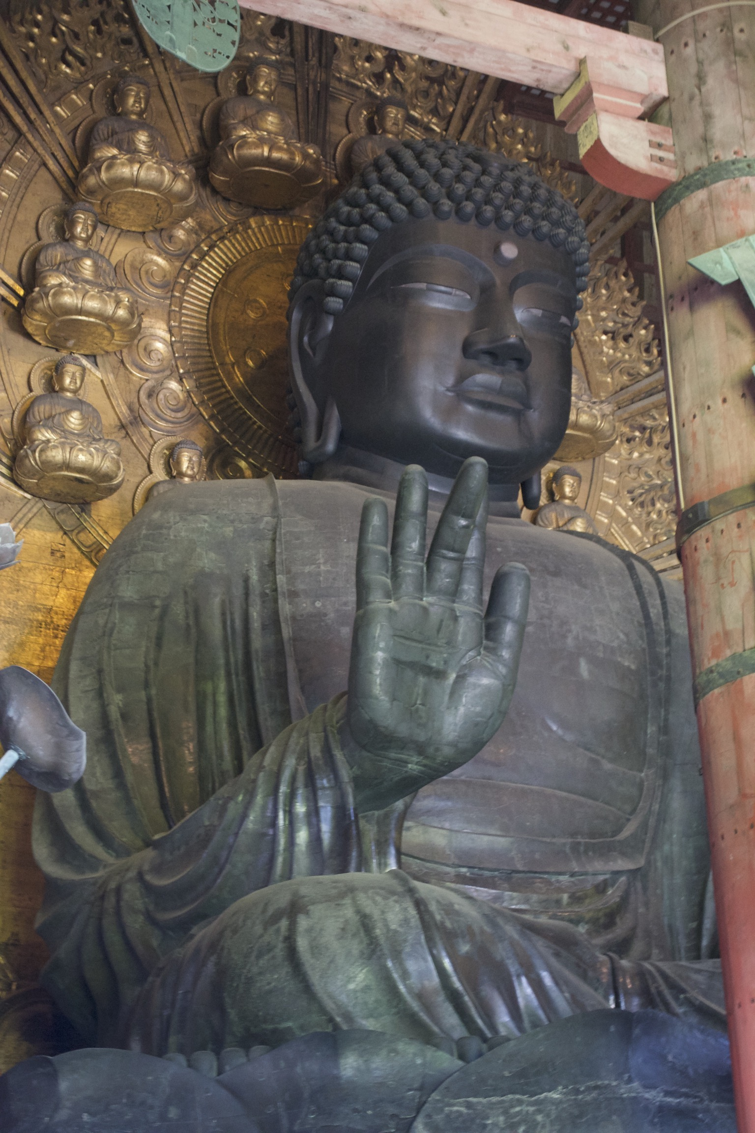 A bronze buddha with its right hand raised, seated before a golden backdrop of seated buddhas.