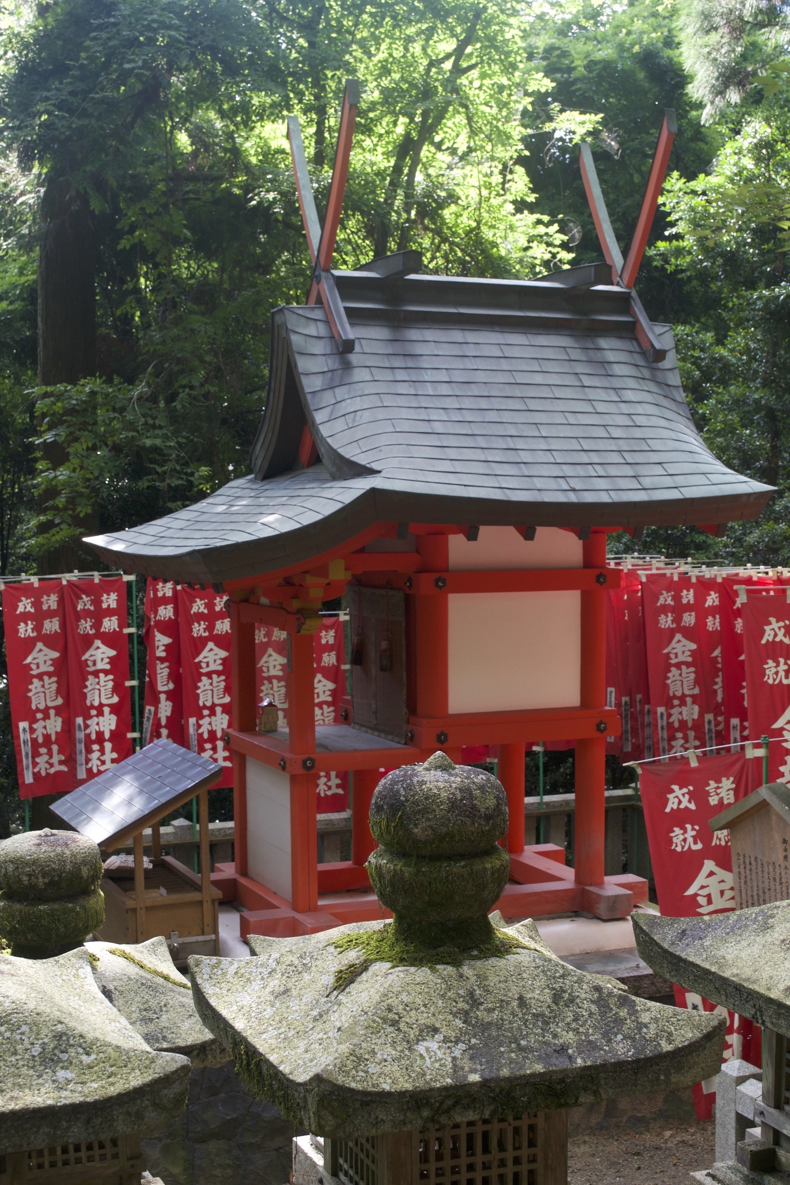 A white shrine with red trim and a slanted black roof sits before some mossy stone monuments.  Red banners with white lettering hang before the trees in the background.