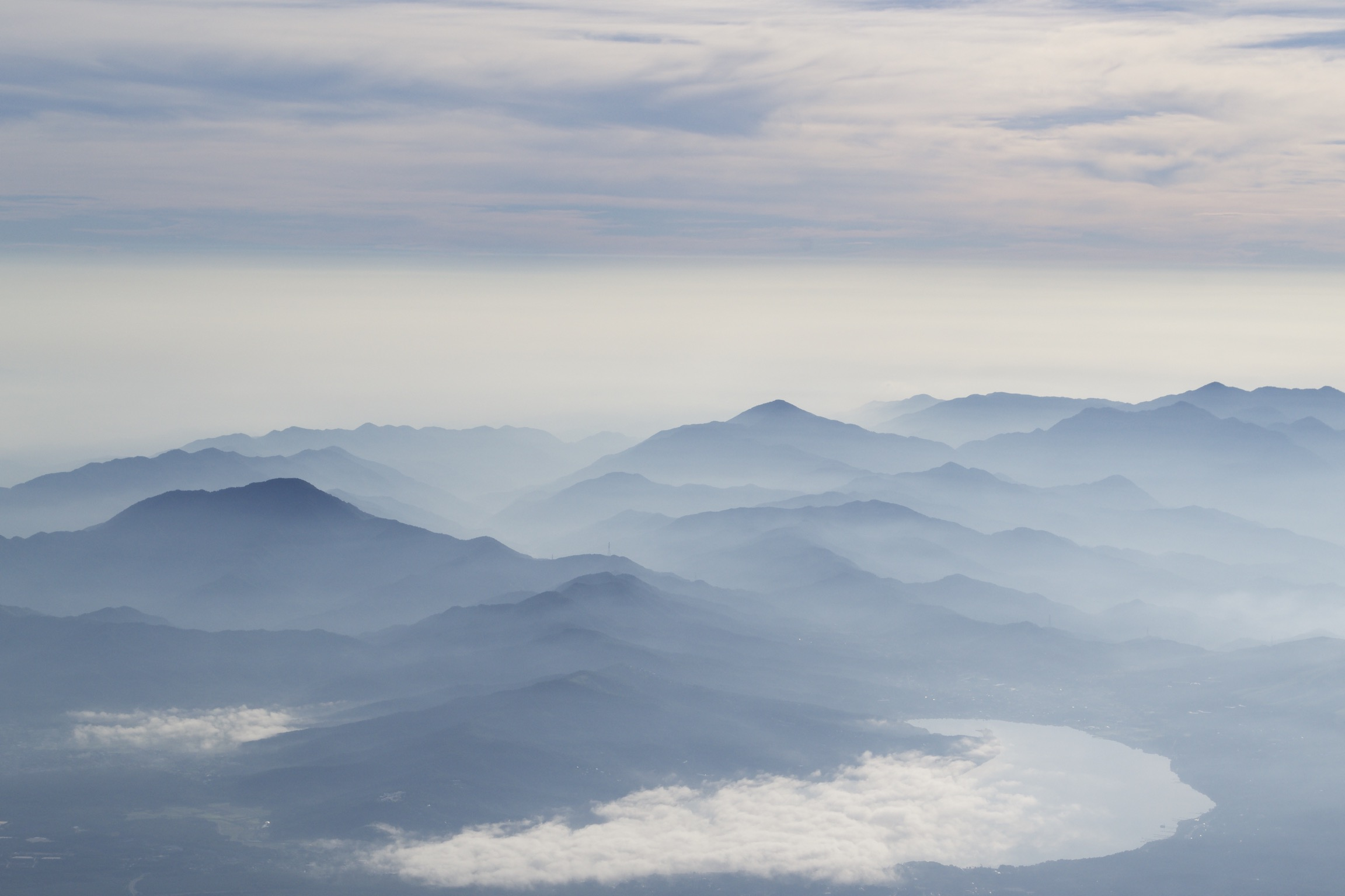 Silhouettes of mountains beneath a cloudy, pastel blue sky.