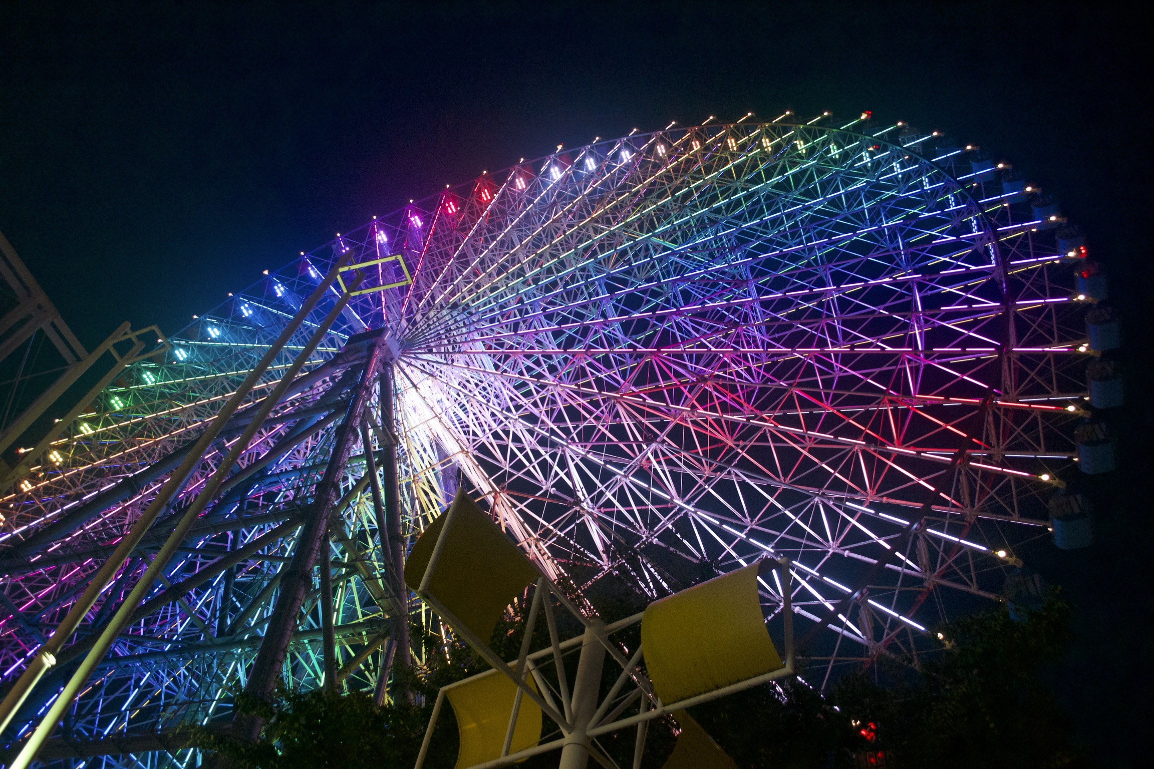 A ferris wheel is illuminated with a rainbow of colors.