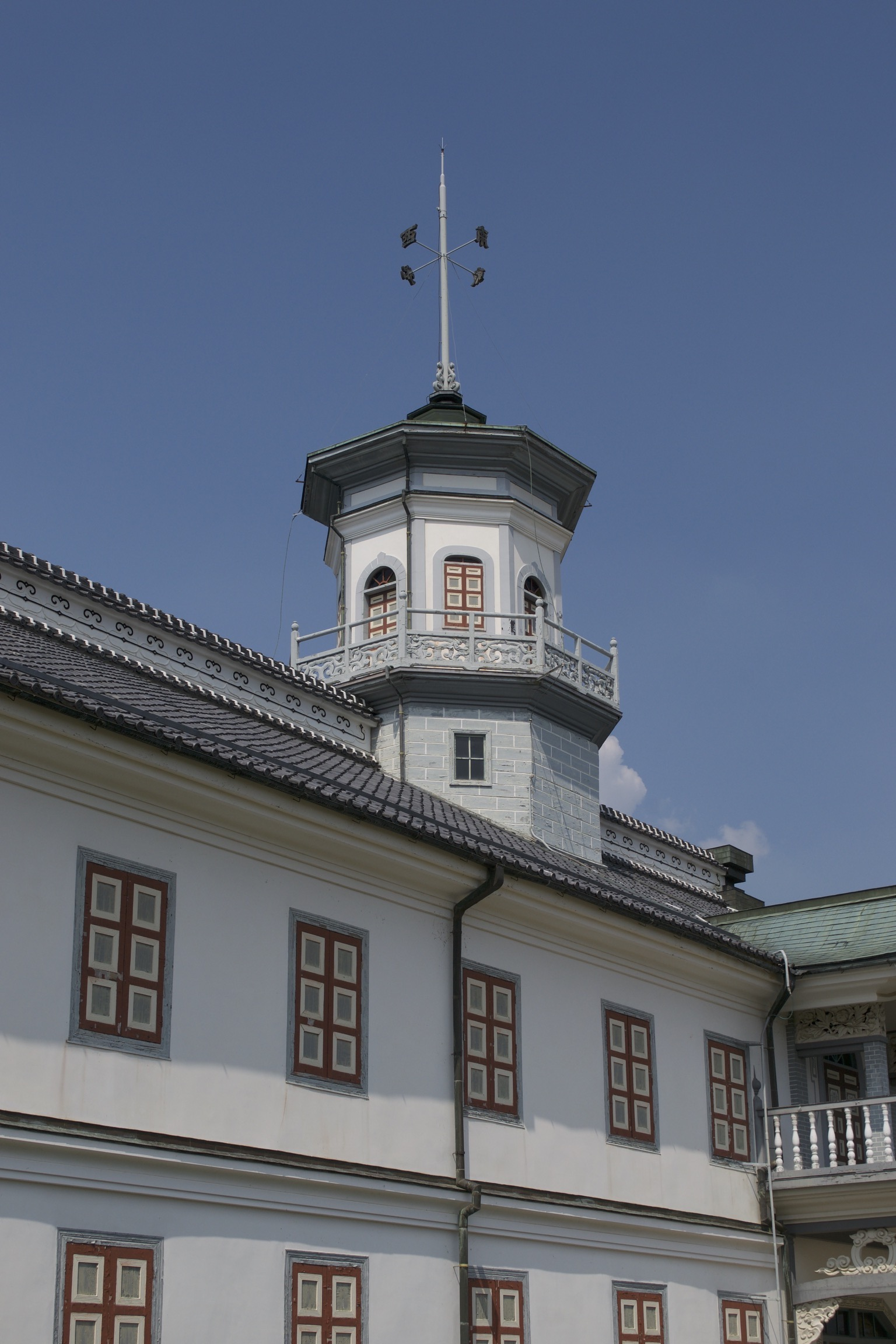 An octagonal tower atop a low, wide western-style building with Japanese elements.