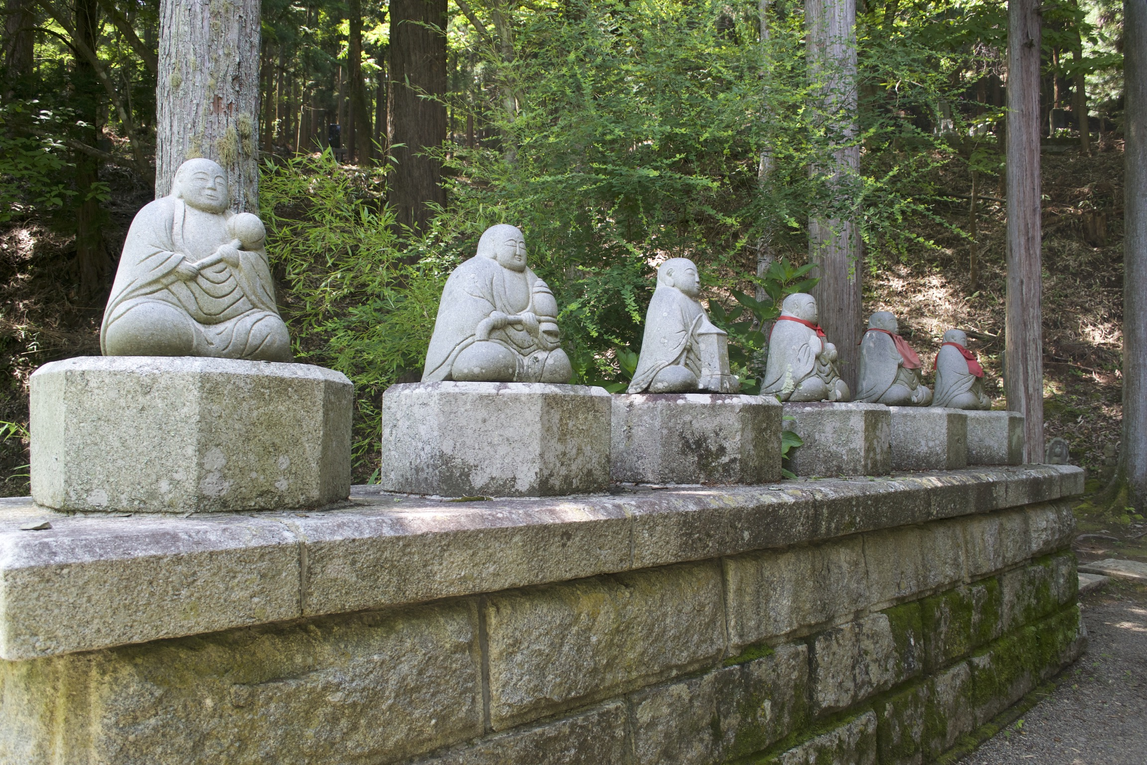 Six stone buddhas sit cross-legged, some with red cloth bibs.