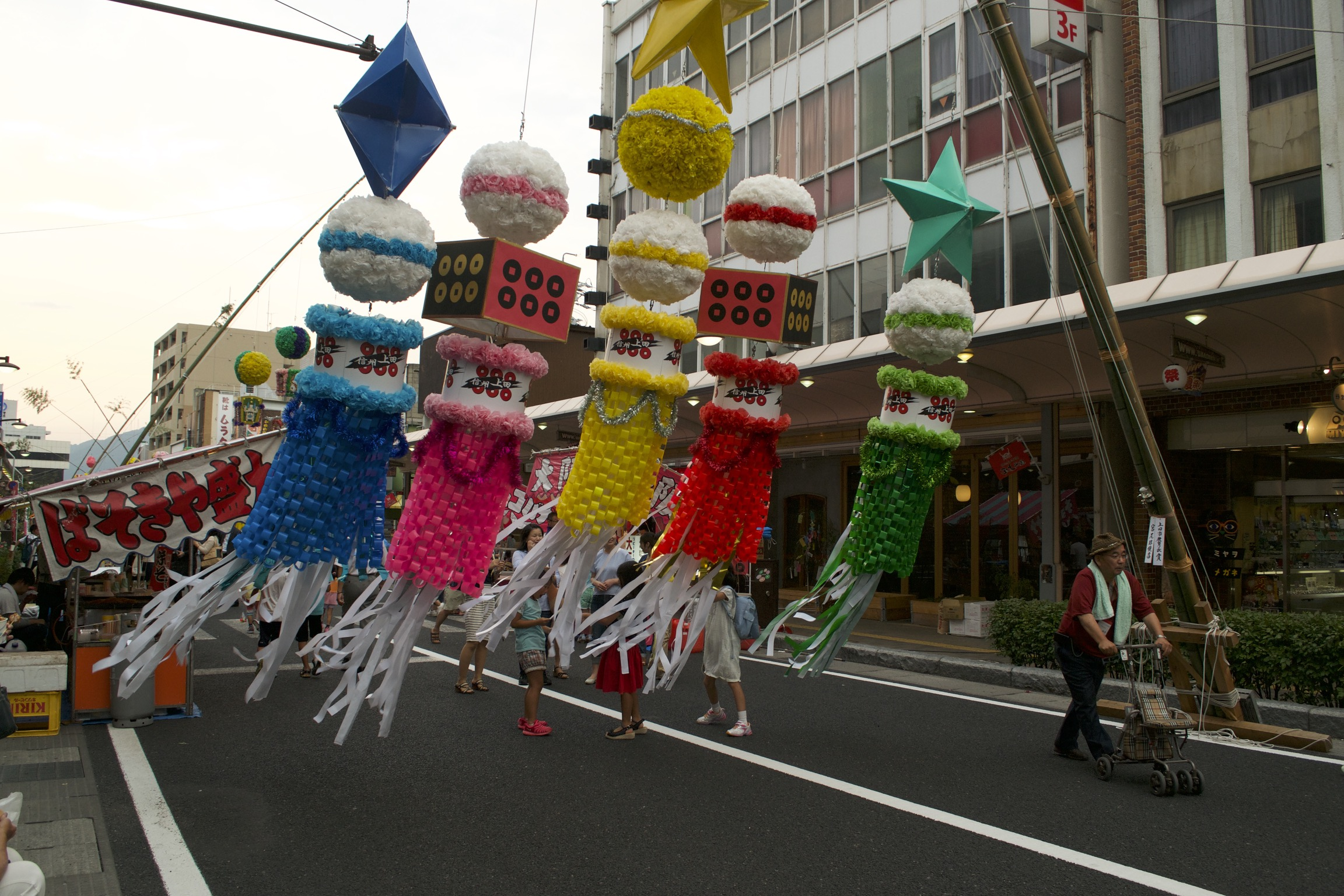 Five large, brightly-colored piñata-like objects hang in the middle of a street.