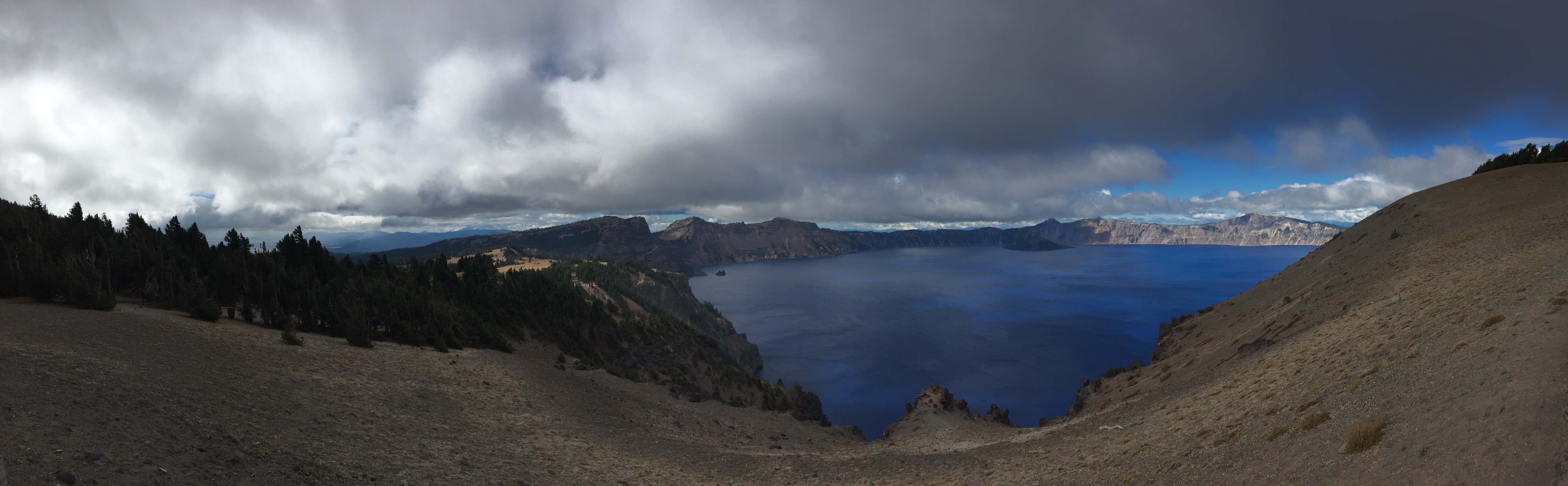 A panorama of the deep-blue Crater Lake and the ominous clouds above.
