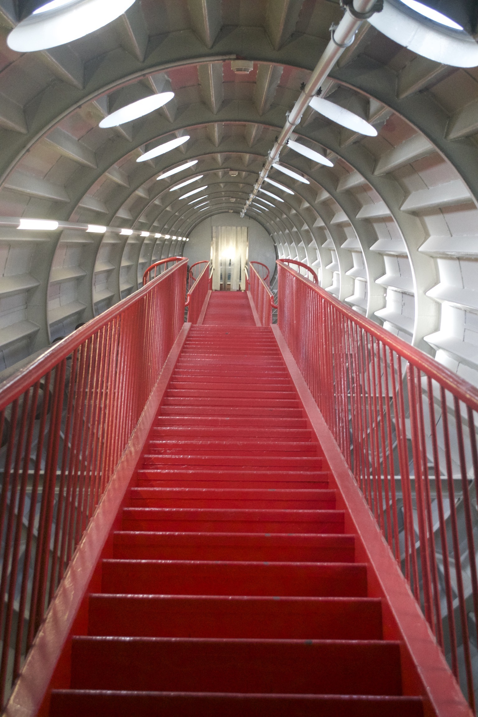 Two flights of red stairs go up a cylindrical tube.