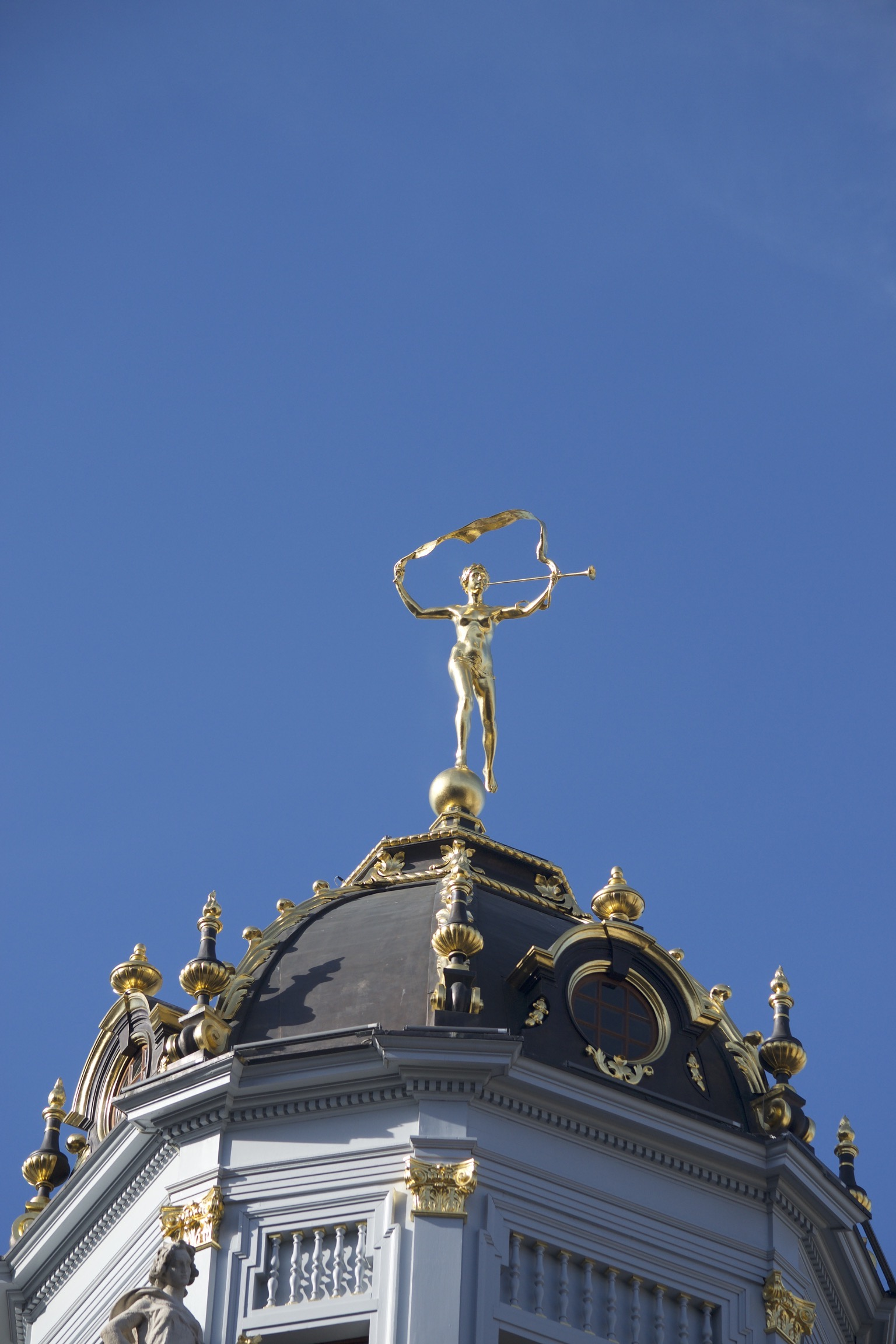 A golden figure blows a trumpet and holds a long ribbon atop a black and gilted roof dome.