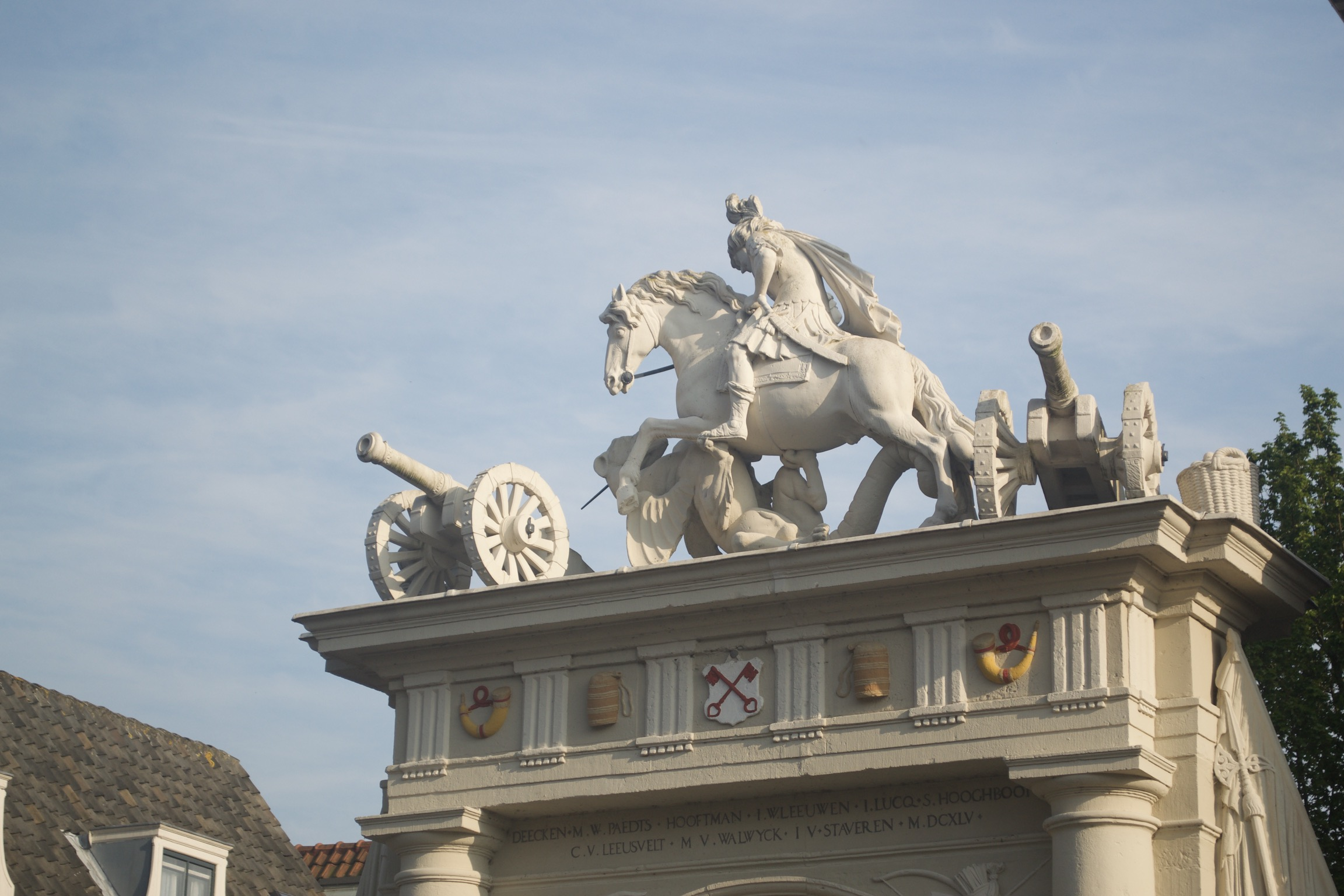 Statues of two cannons and a horse and rider fighting a griffin on top of an archway.