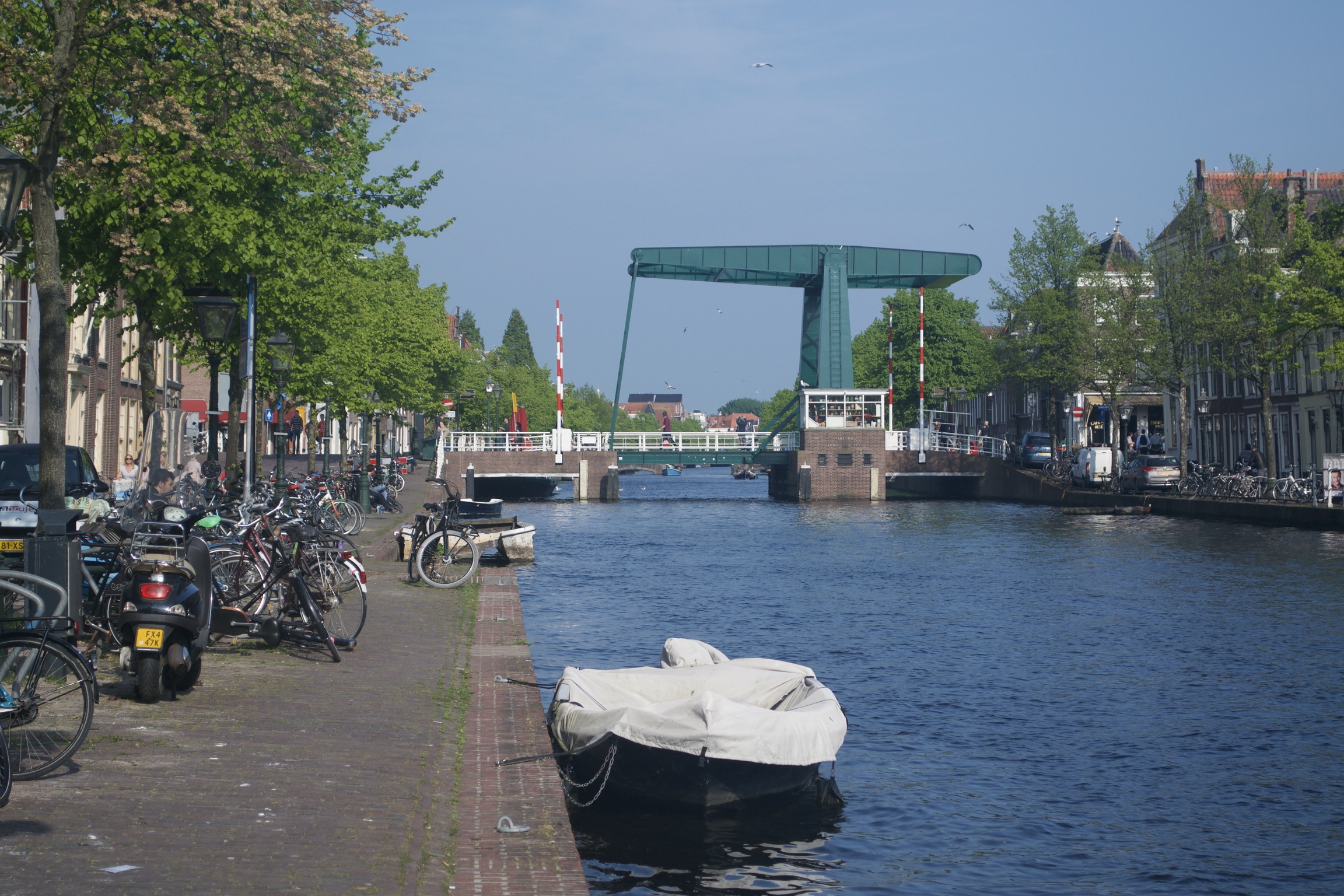 A boat tied up on the side of a canal, with a cantilevered drawbridge in the background.