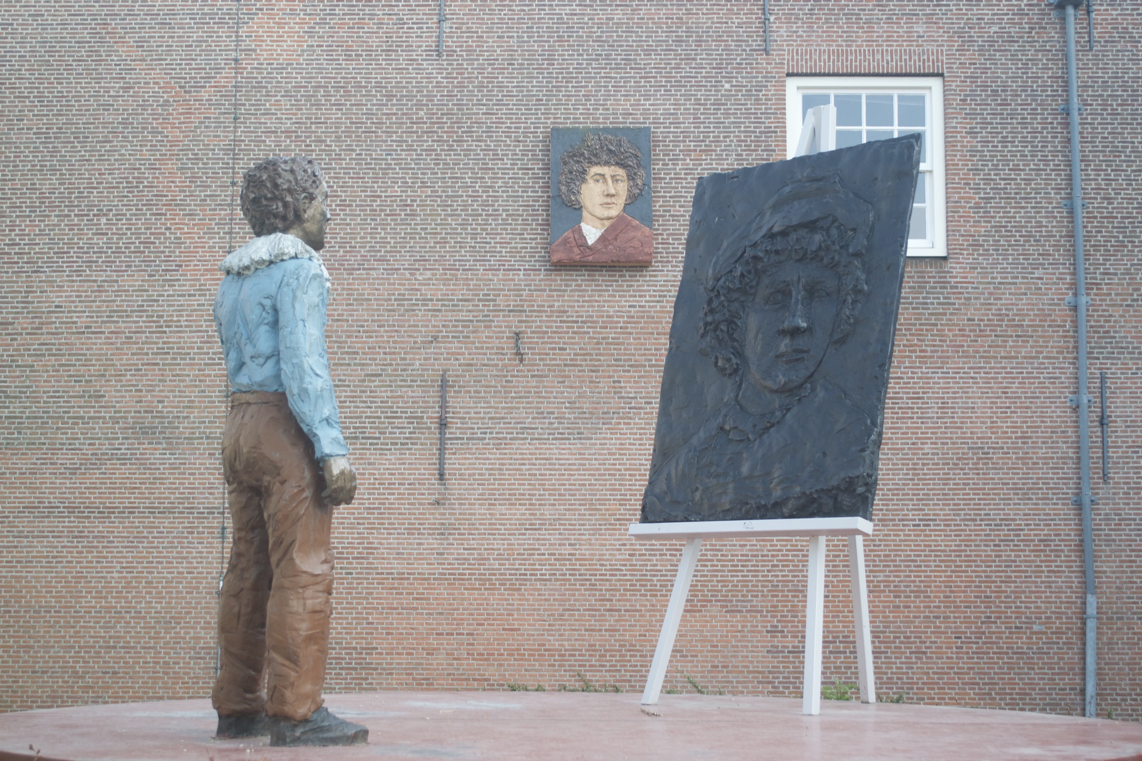 A statue of a man looking at a canvas with another man's face.  That same image hangs on a wall in the background.