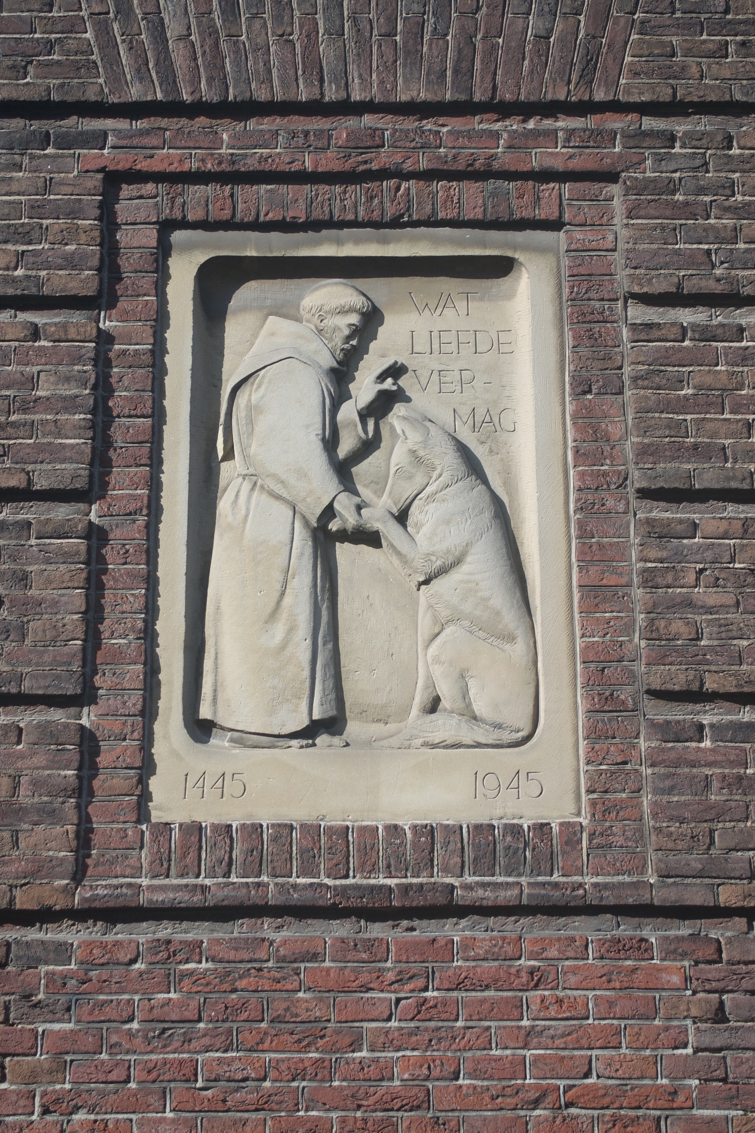 A carving of a monk blessing a dog, inscribed with the dates 1445 and 1945 in the bottom corners and