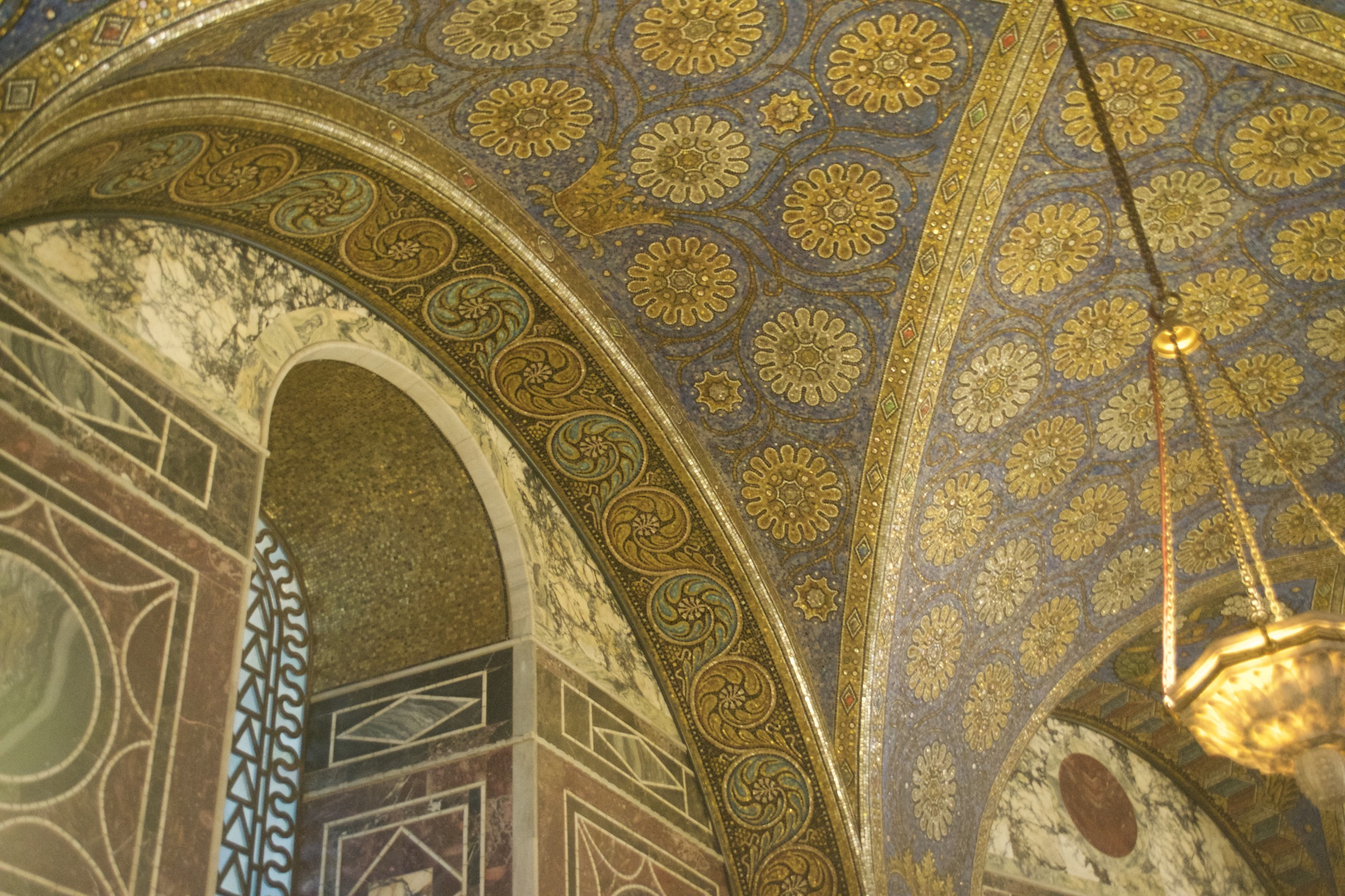 Marble and tile mosaics cover a ceiling and window arch in geometric and flowered designs.