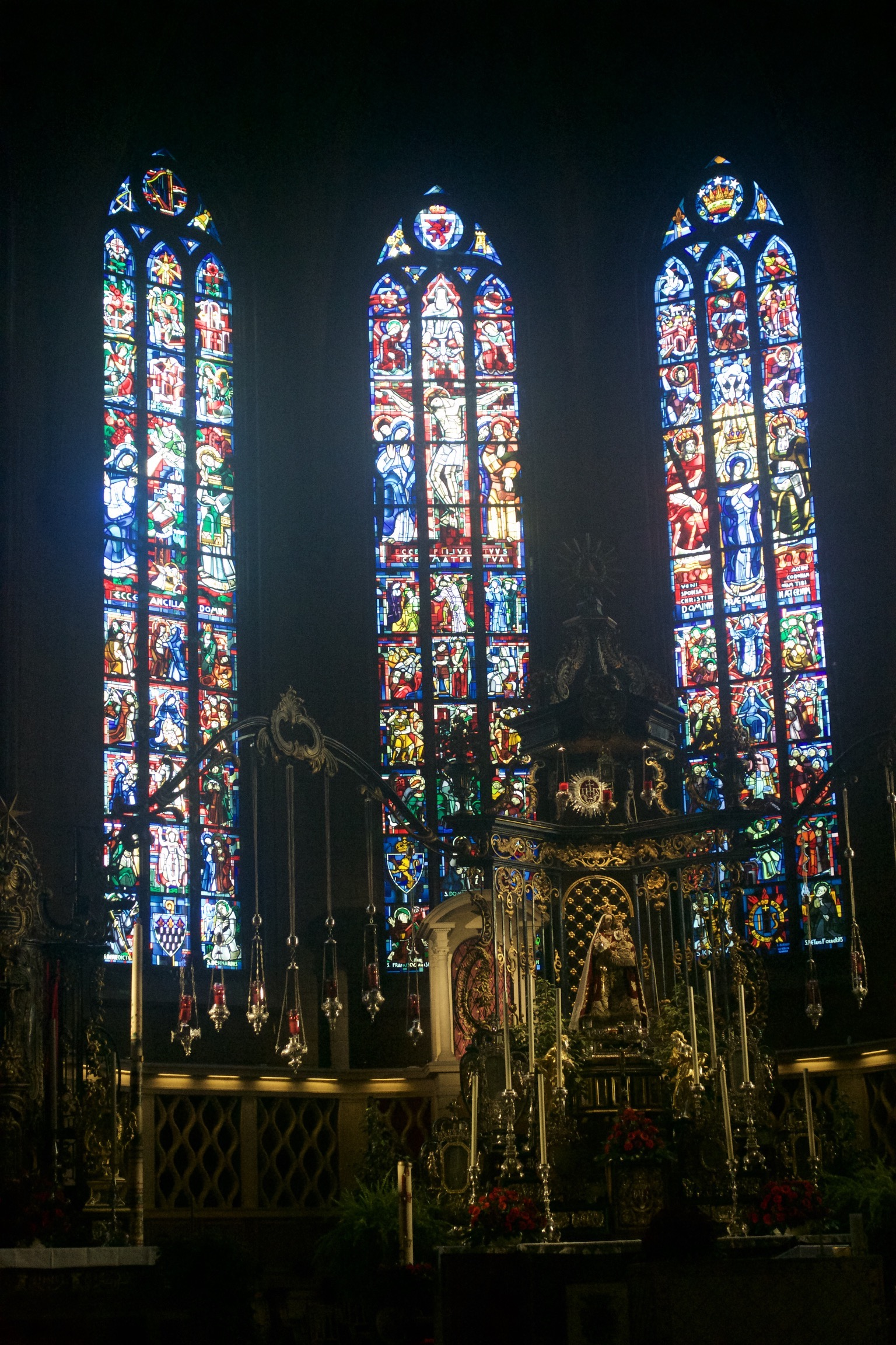An ornate Catholic altar back lit by soaring stained glass windows.