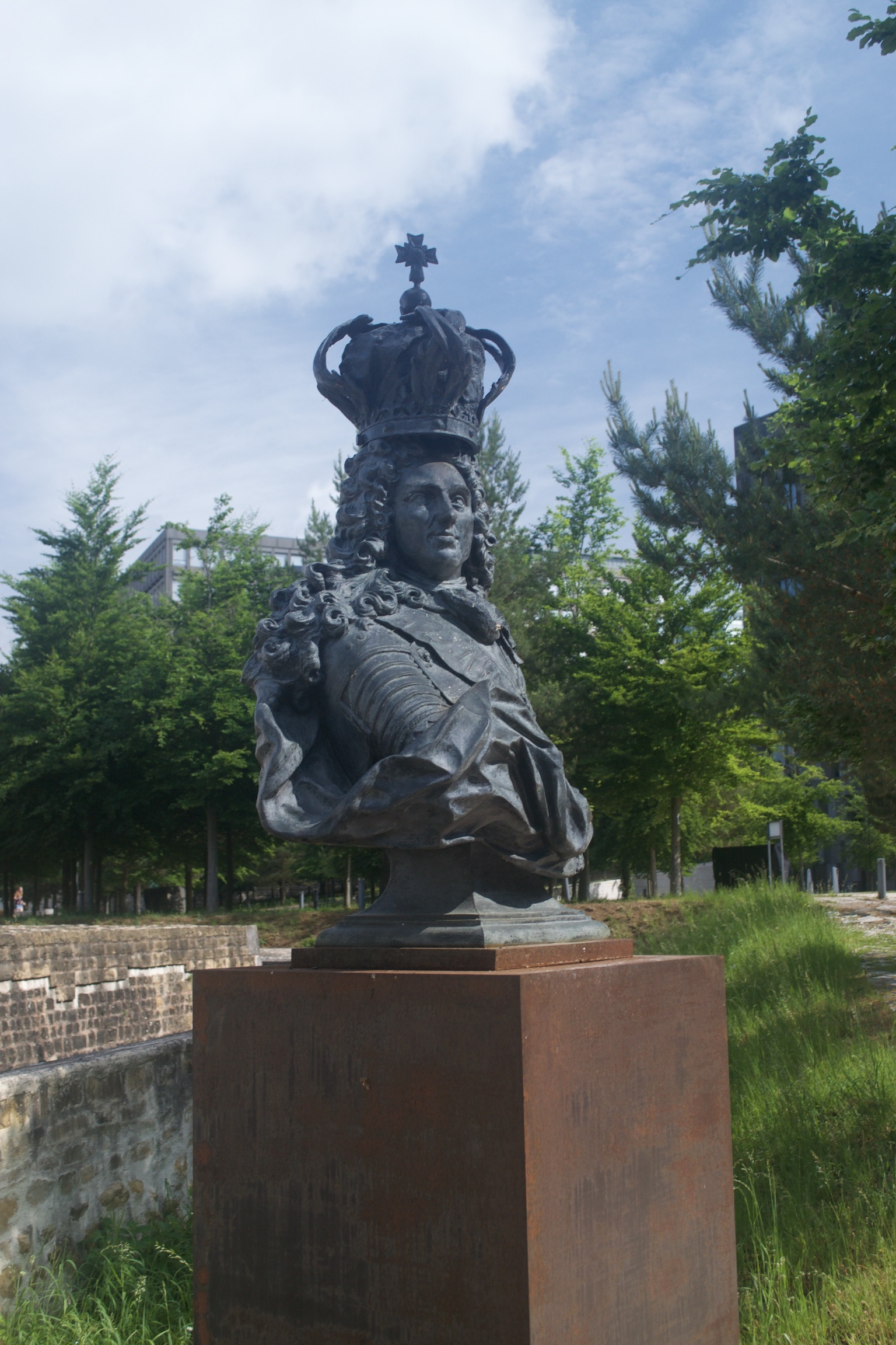 A bronze bust atop a rusted plinth.  A crown sits above the subject's hair, rather than on his head.