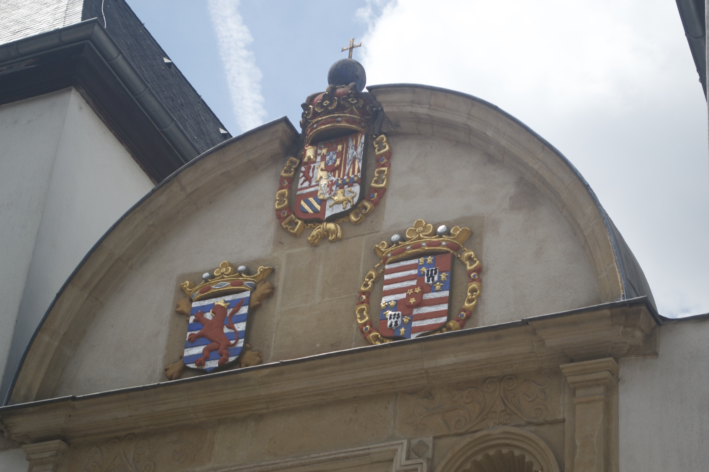 Three coats of arms, all red, yellow, and gold with lions, star, stripes, and crowns on a brown stone building.