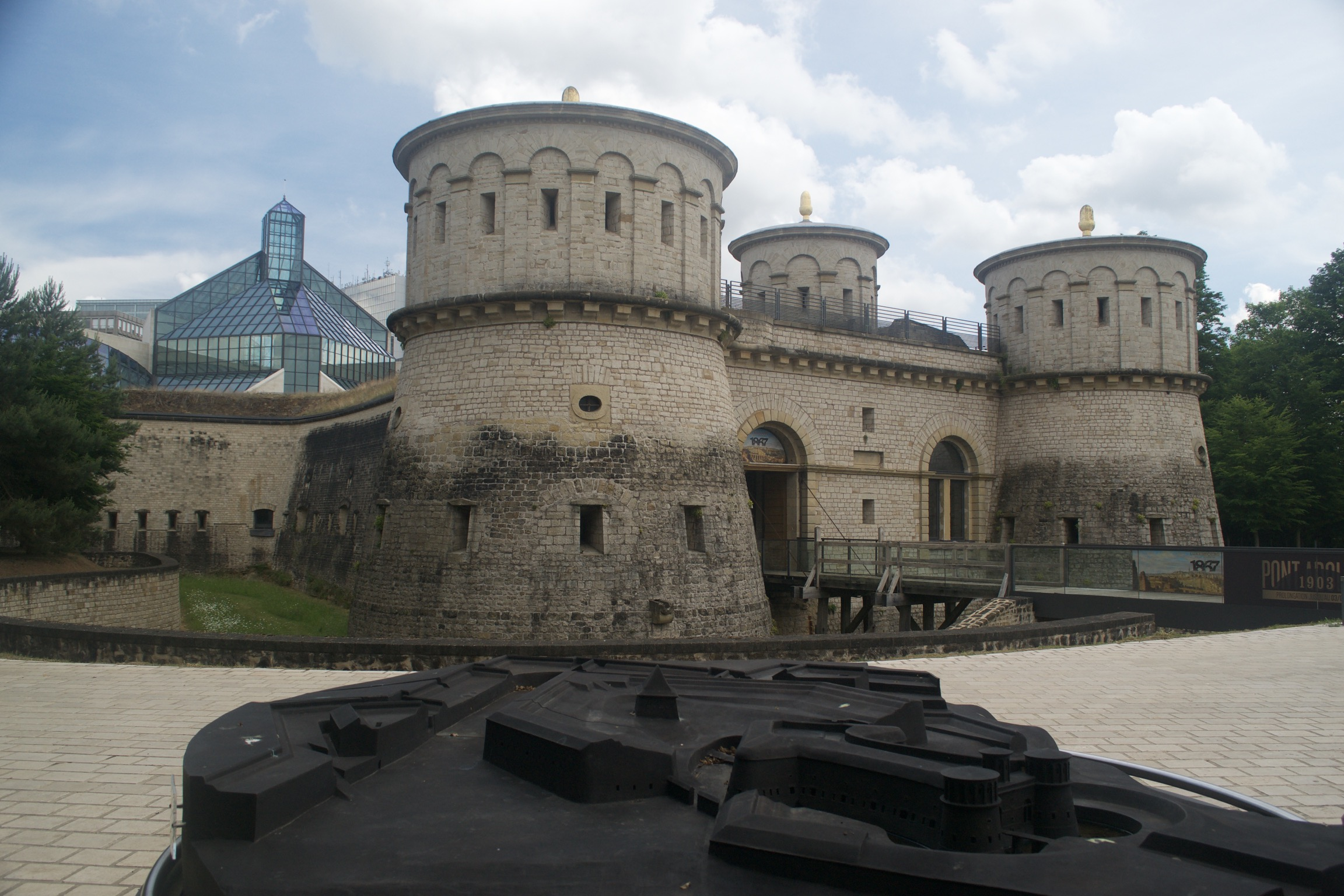 A fortress with three large round turrets, each with a golden orb on top, in front of a tall glass building in the background.