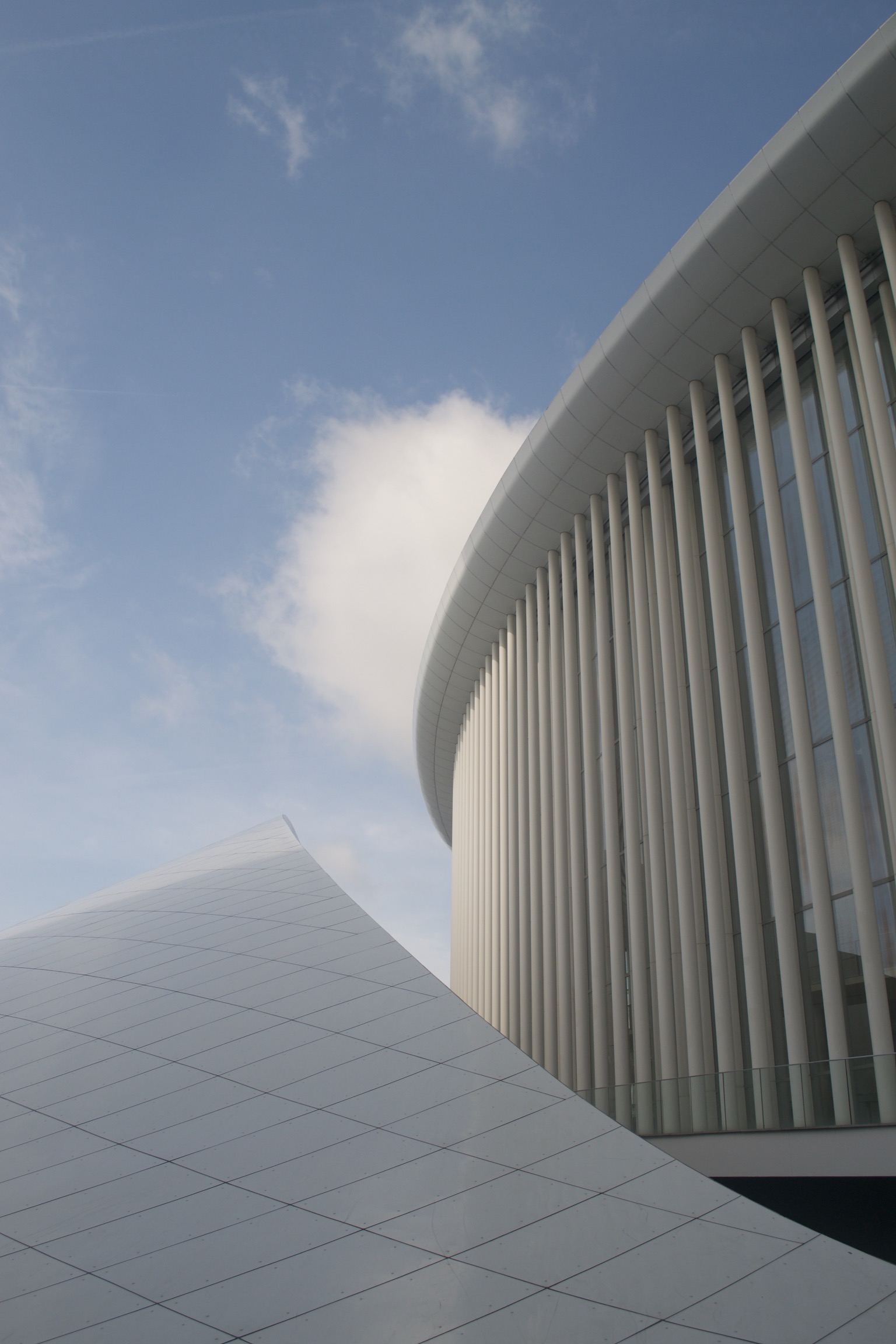 A white paneled slope wraps around a tall, round glass building with white columns and cornice.