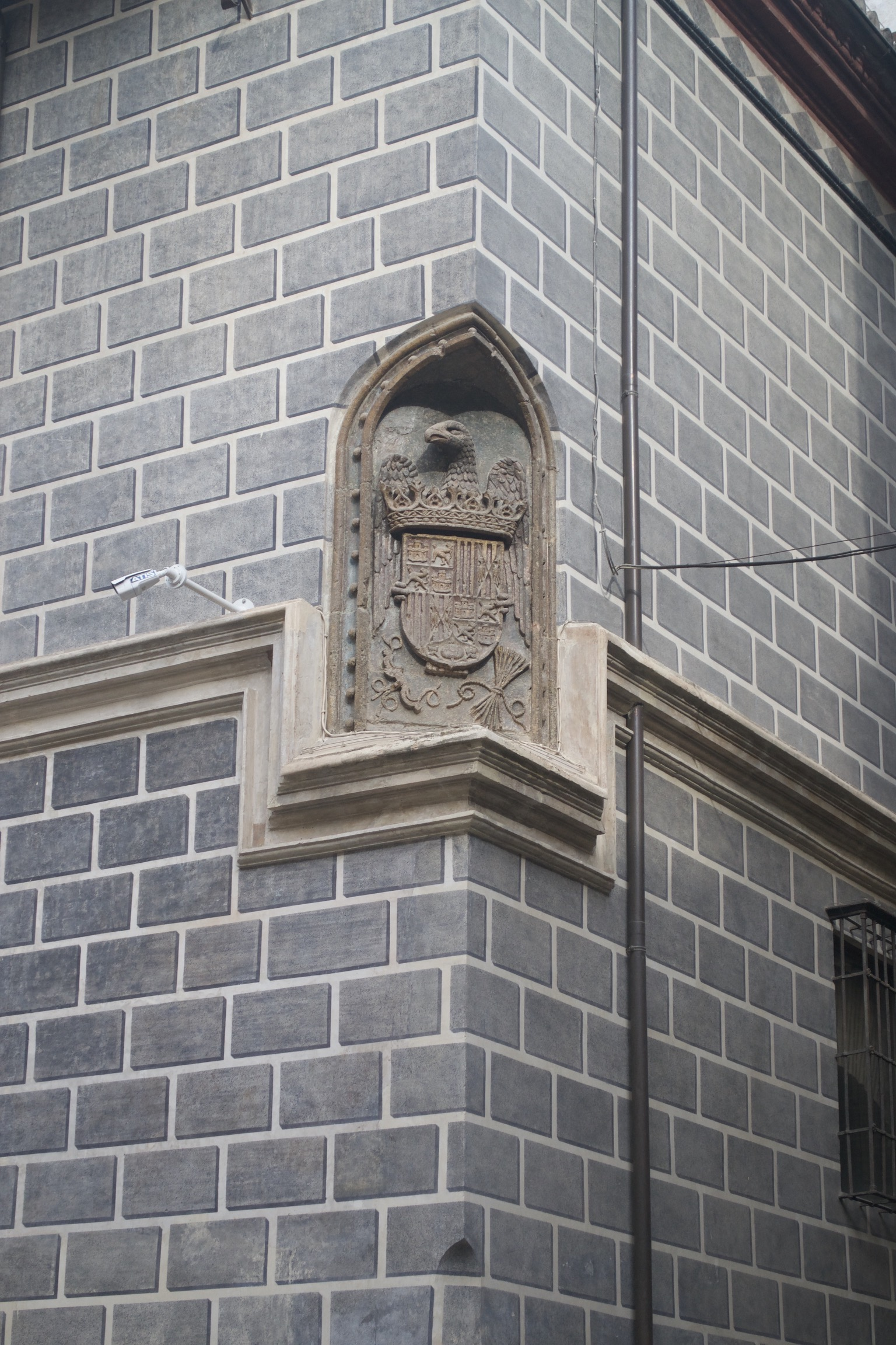 A coat of arms is built into the corner of a gray brick building.