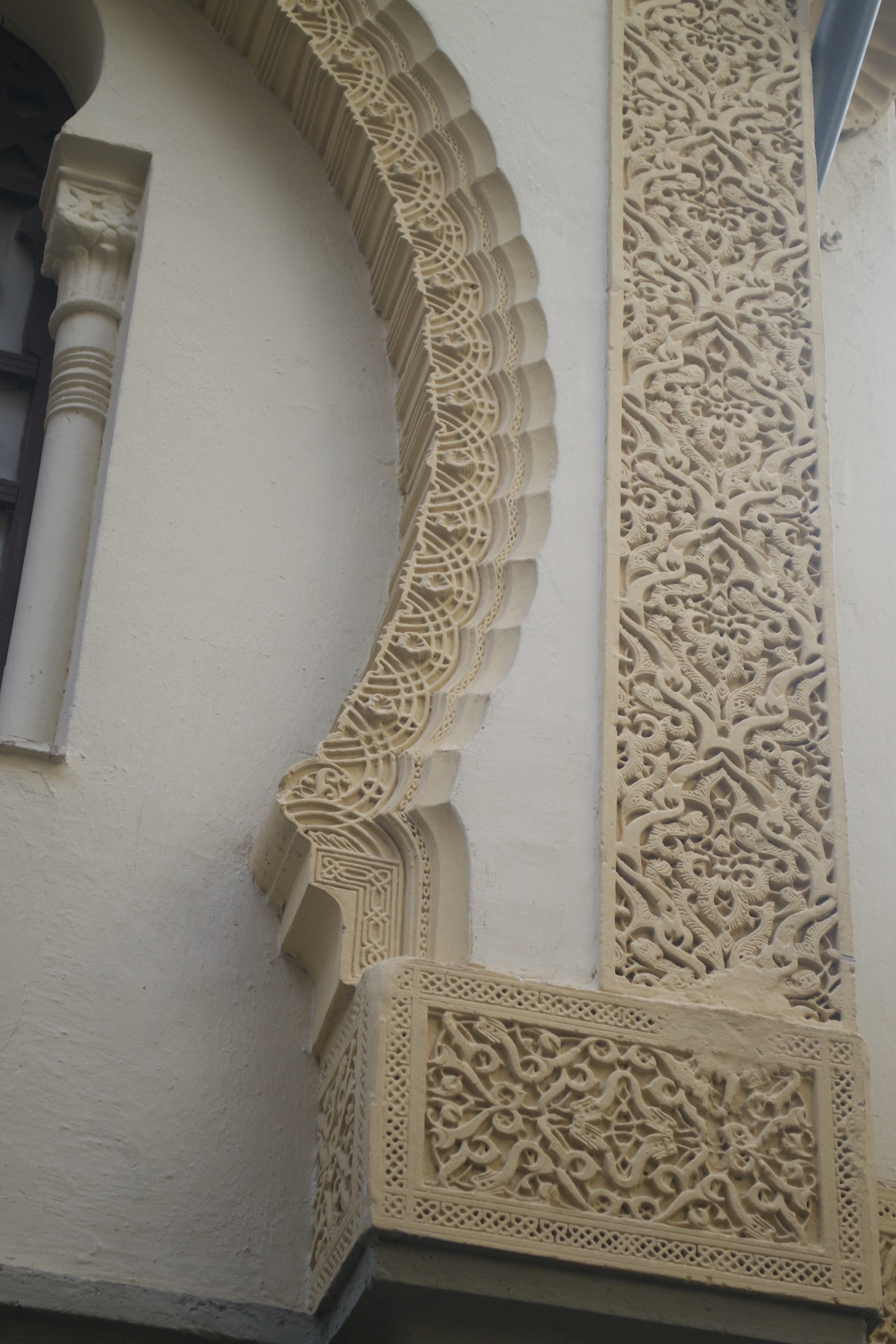 Delicate geometric carvings surround a window.