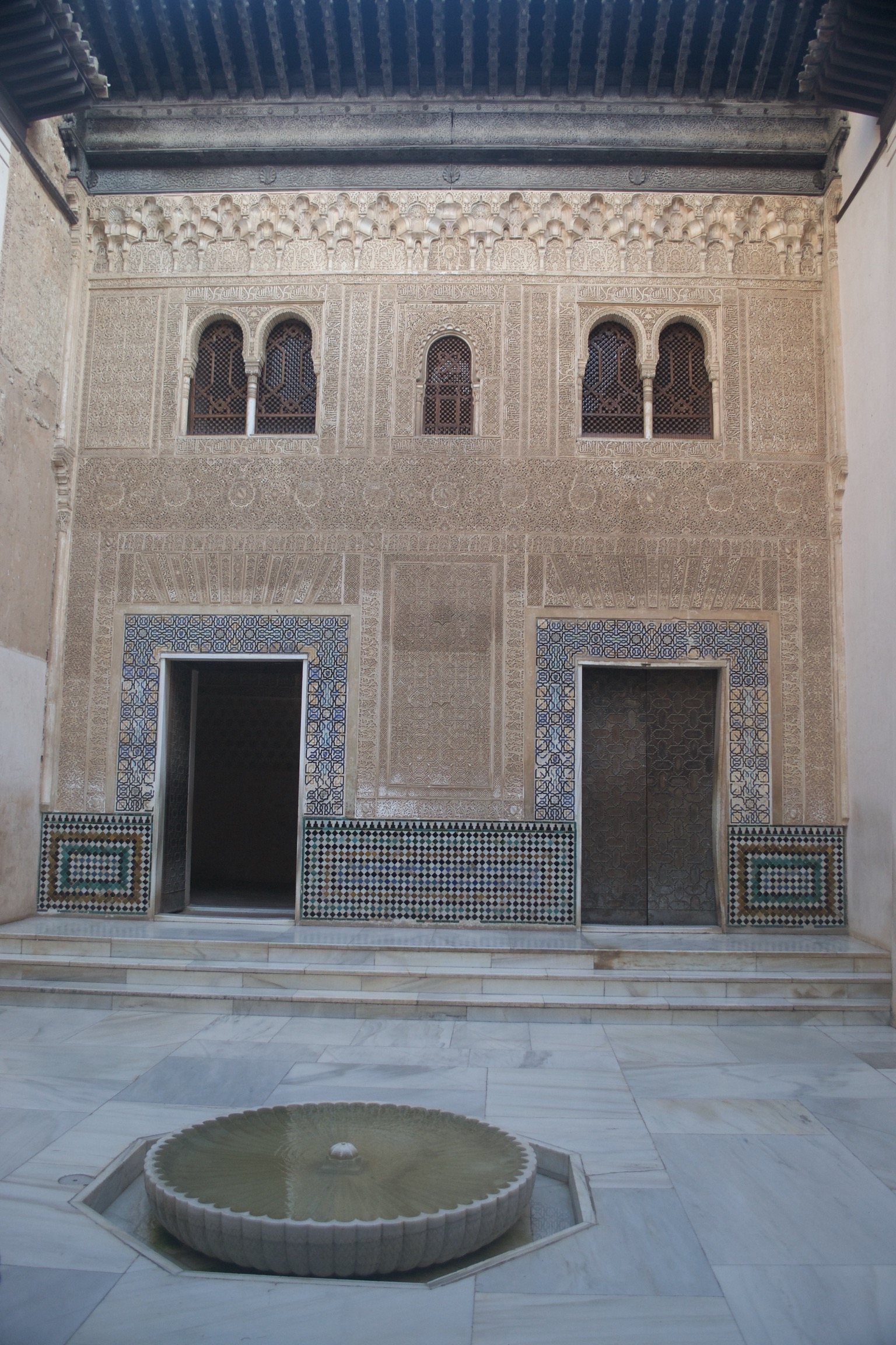 Two doorways are surrounded by mosaics.  The wall is covered with plastered molds or carved engravings.