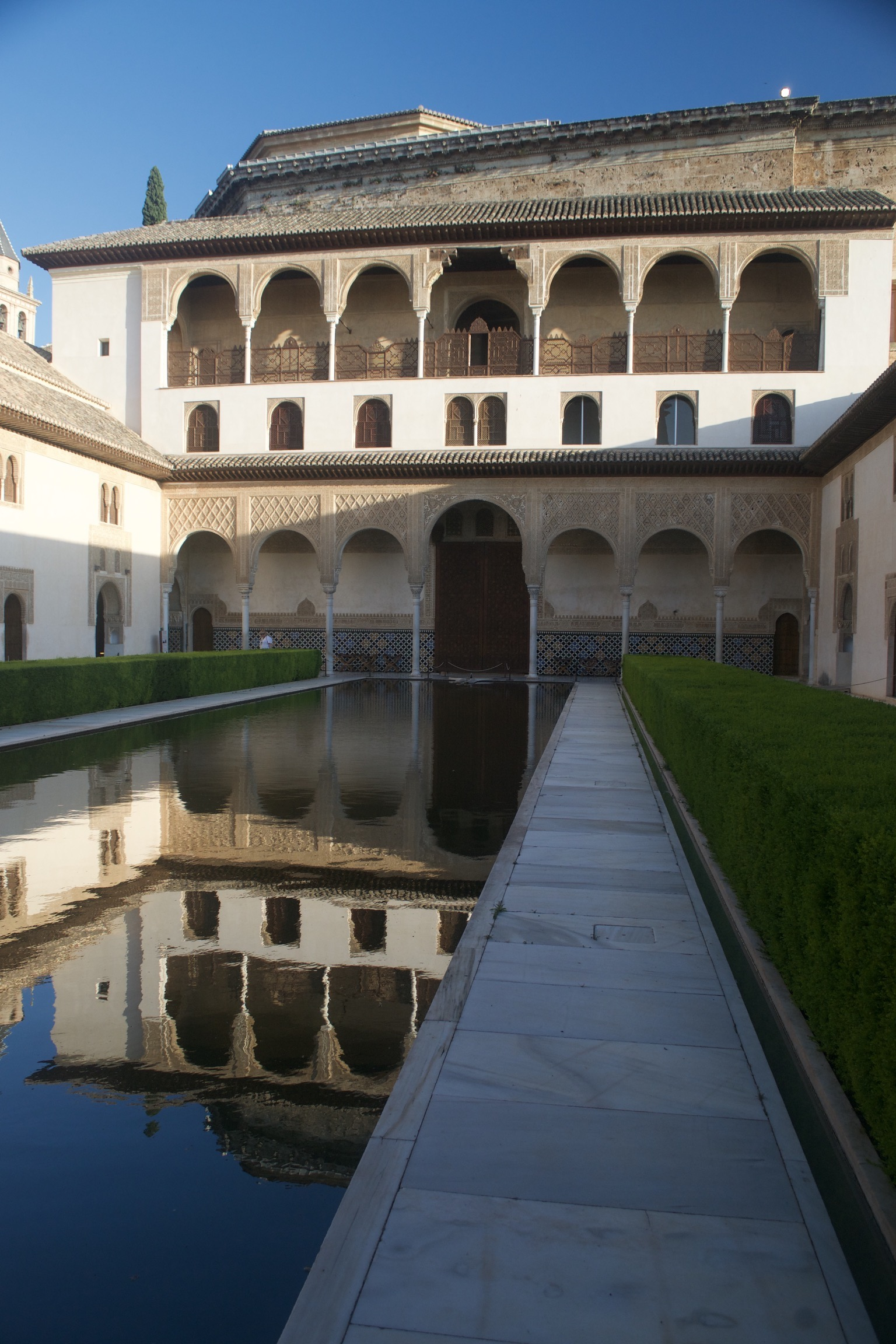 A still reflecting pool mirrors a surrounding two-storied building.