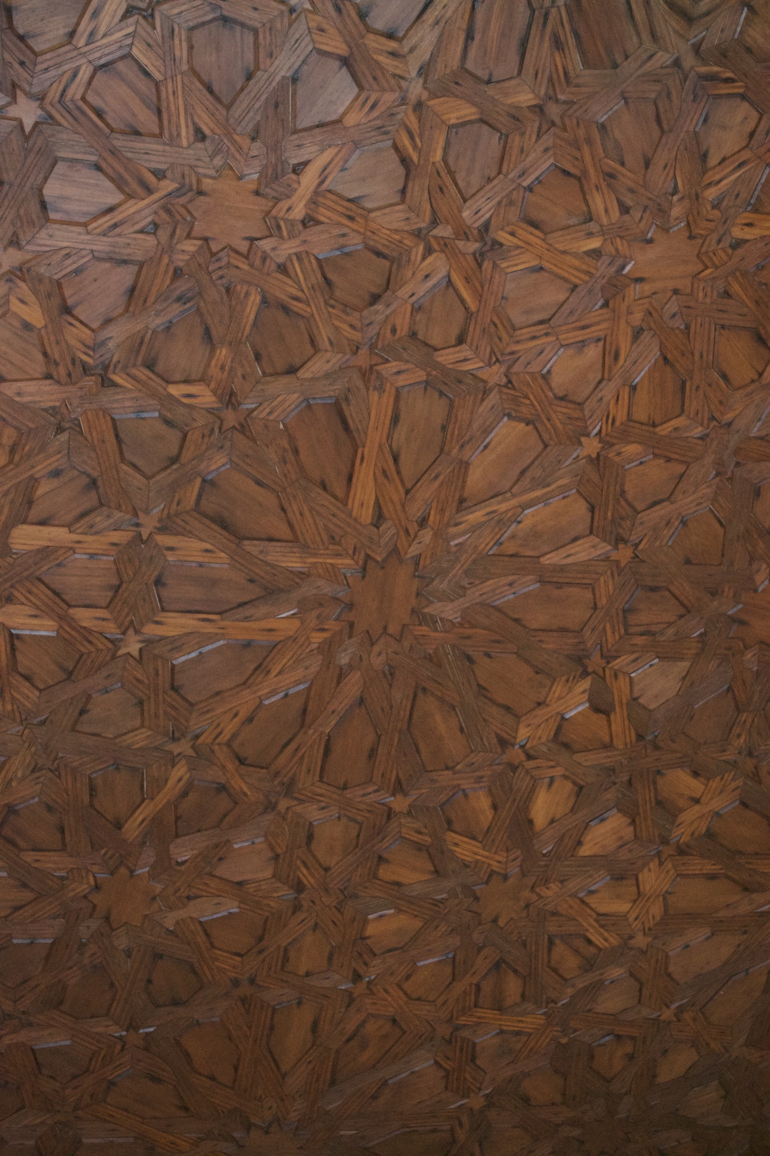 A geometric design of inlaid eight- and five-pointed stars that appear woven in wood.