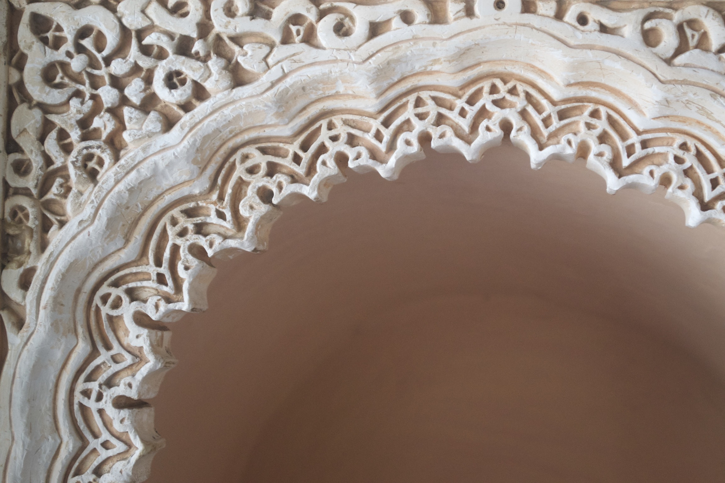 Geometric designs surround a scalloped archway.