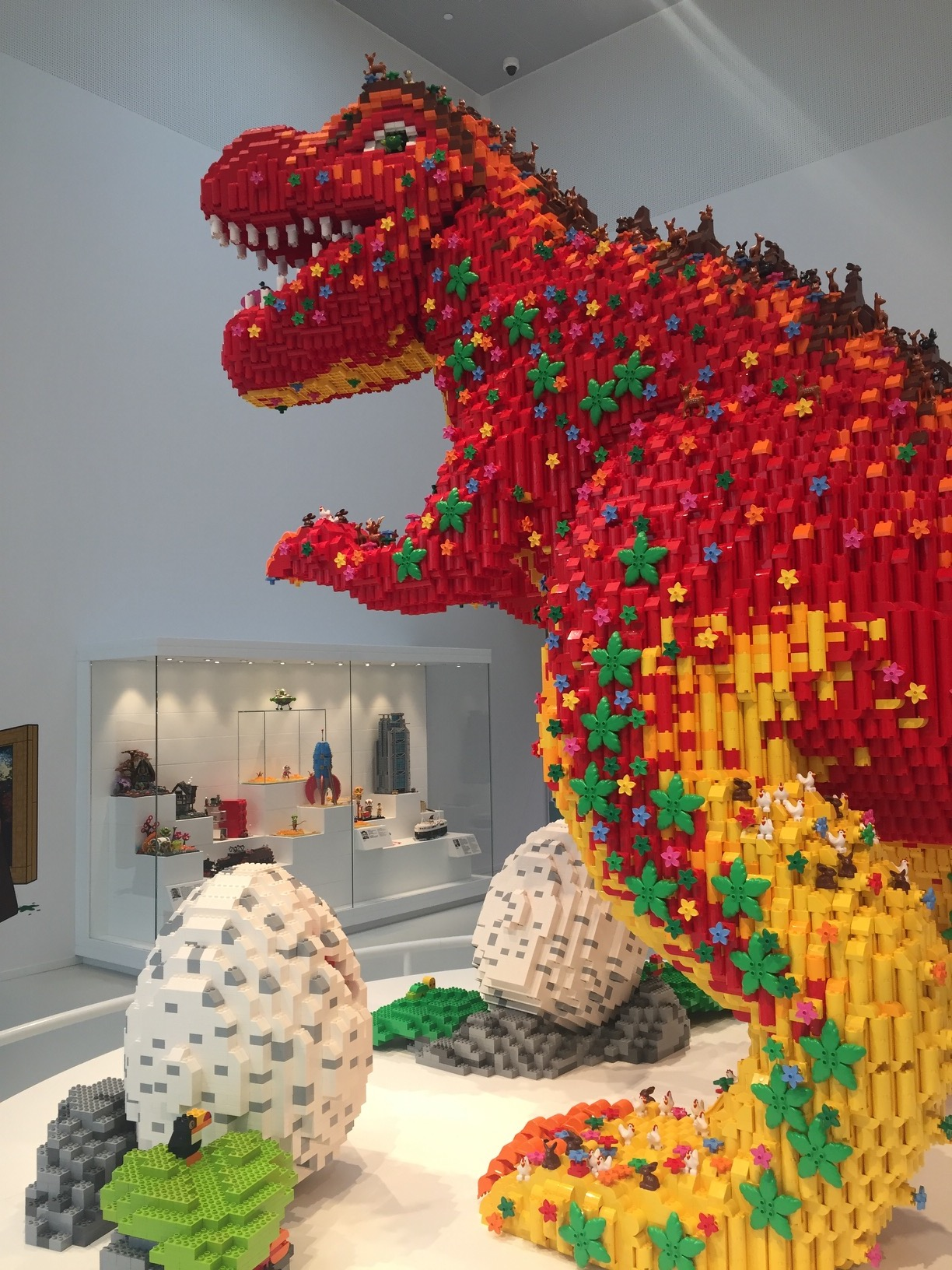 A more whimsical red-and-yellow LEGO dinosaur, with small leaves and animals riding along.