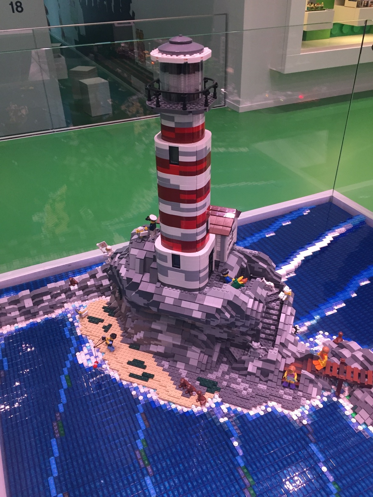 A LEGO lighthouse on a rocky island with a small beach, breaking the waves.