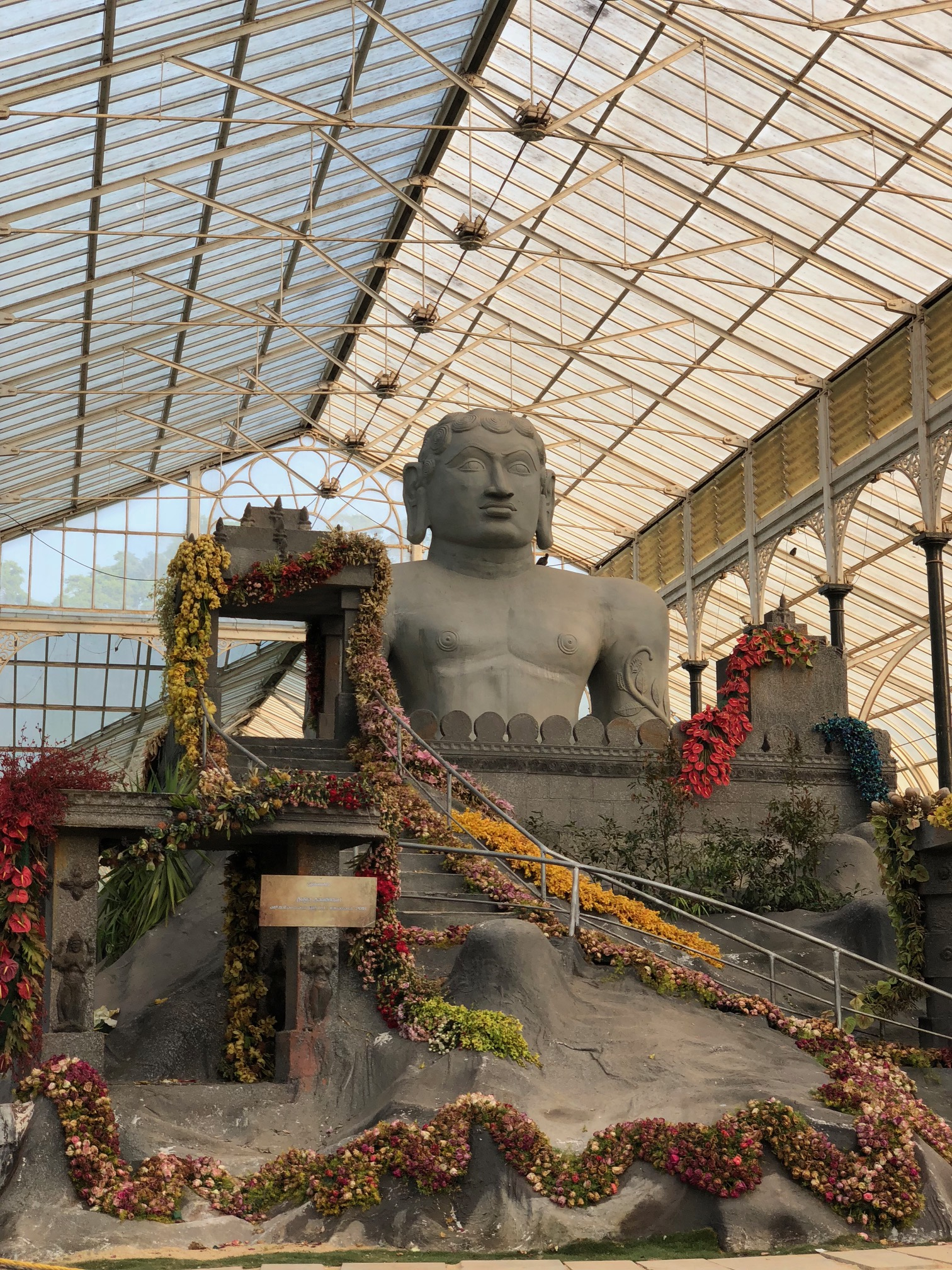 Inside a glass building, an enormous stone figure sits behind a castle wall covered with flowers.