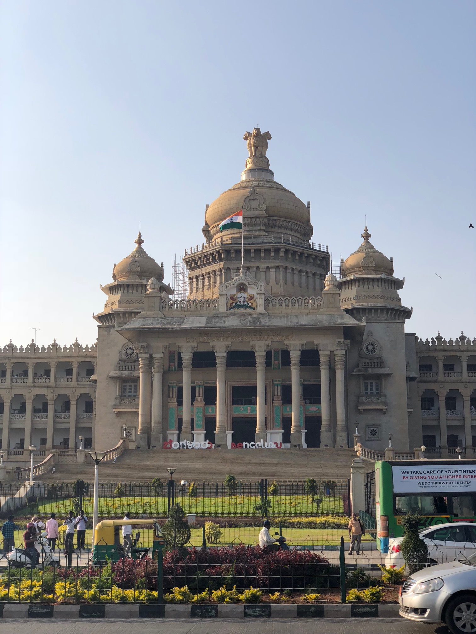 An enormous stone building with columns, culminating in a pointed dome with three lions on top.  The Indian flag of orange, white and green horizontal stripes flies in the breeze.