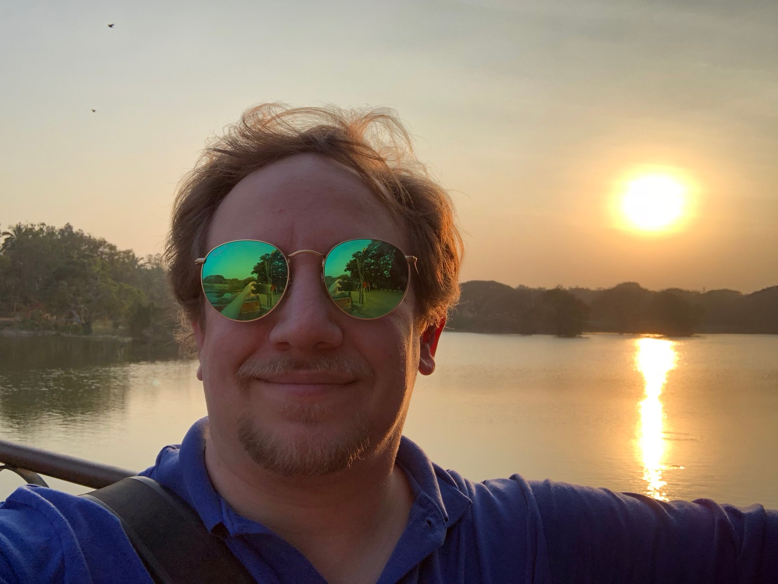 The sun sets over a lake, behind a man with a goatee, messy blond hair, and preposterous sunglasses.