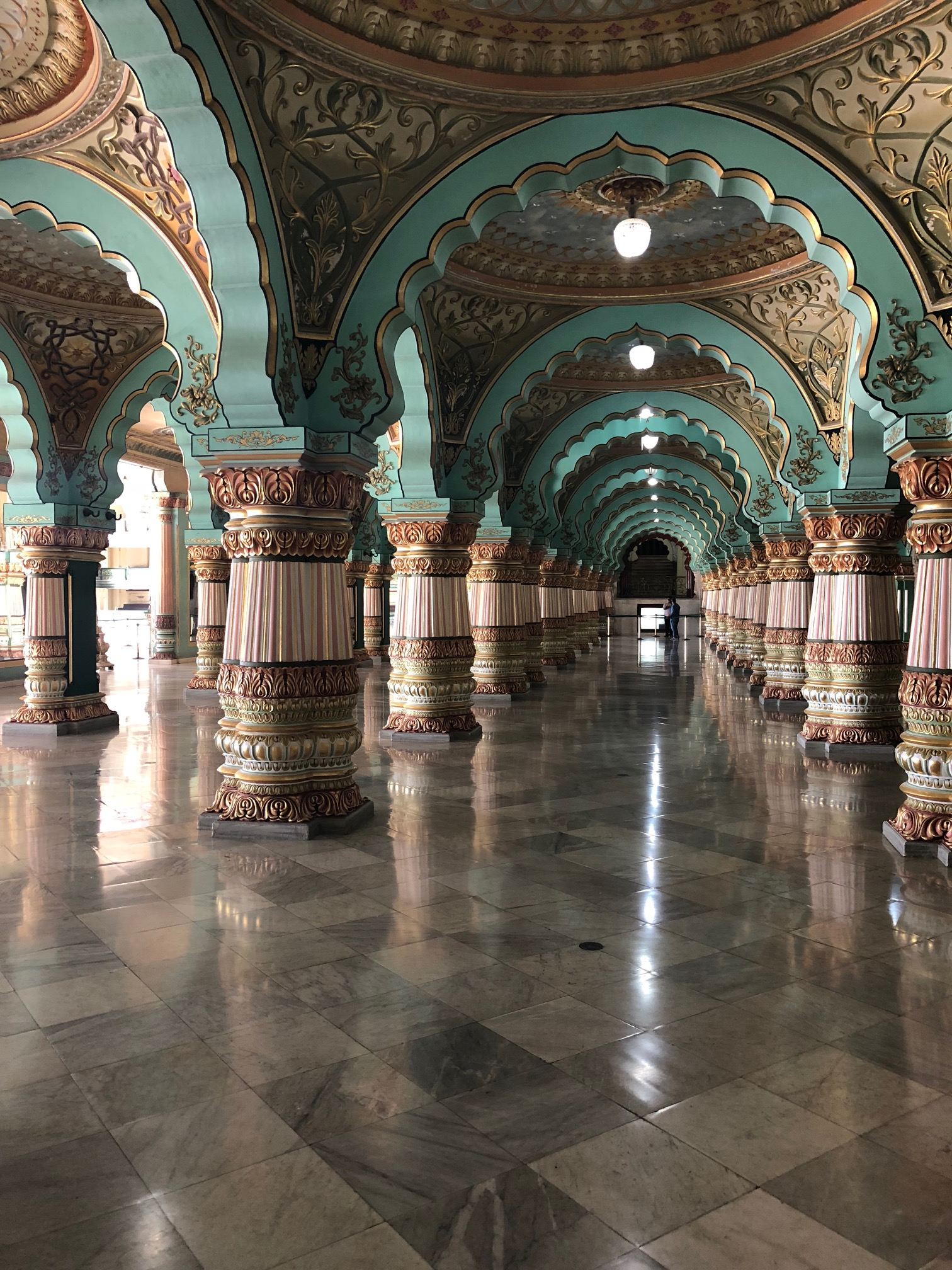 Rows and rows of teal scalloped archways supported by thick ornate columns on a granite floor of large square tiles.