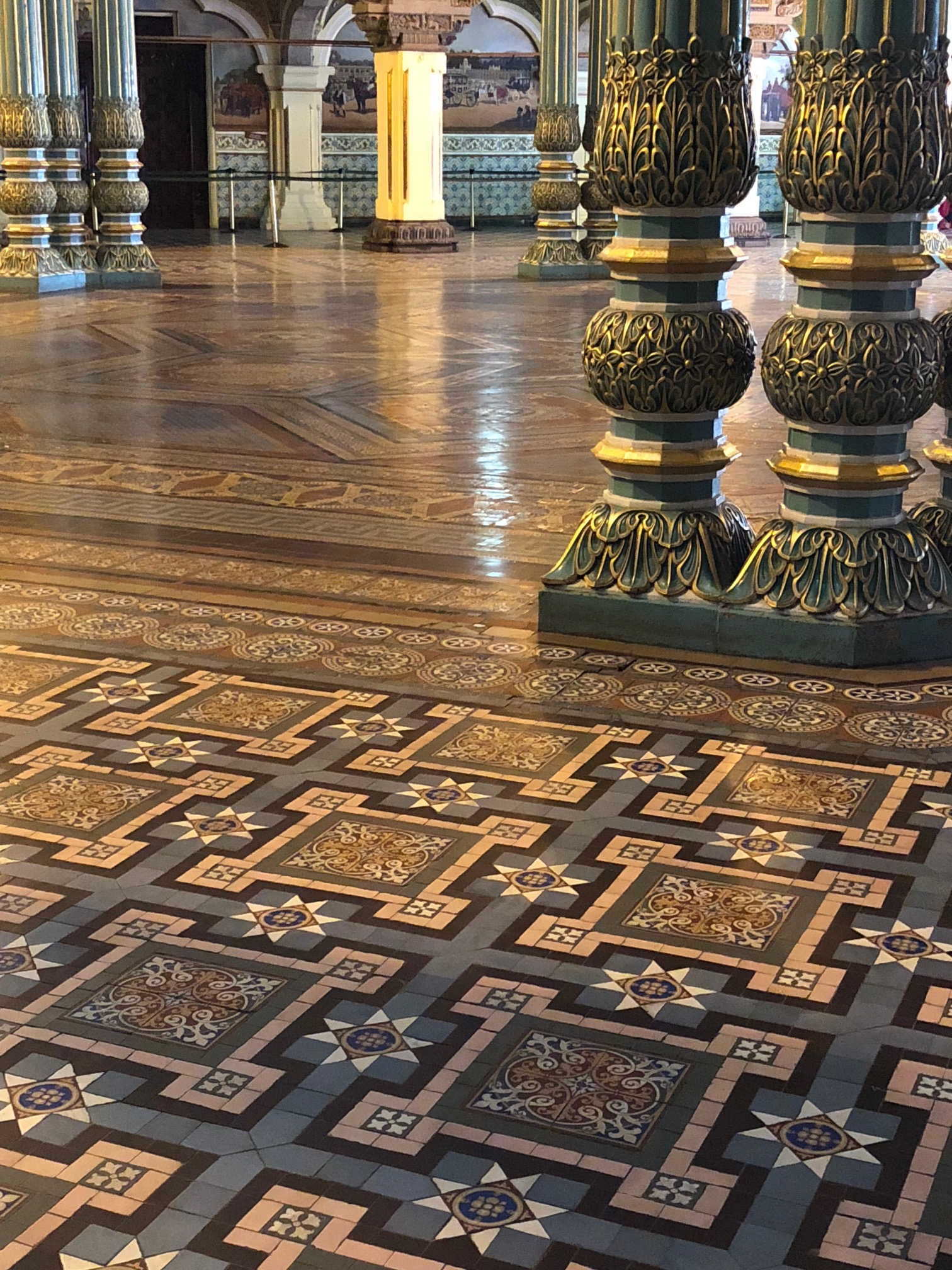 Green columns are painted with gold accents giving the impression of foliage surround a large tiled octagonal floor.