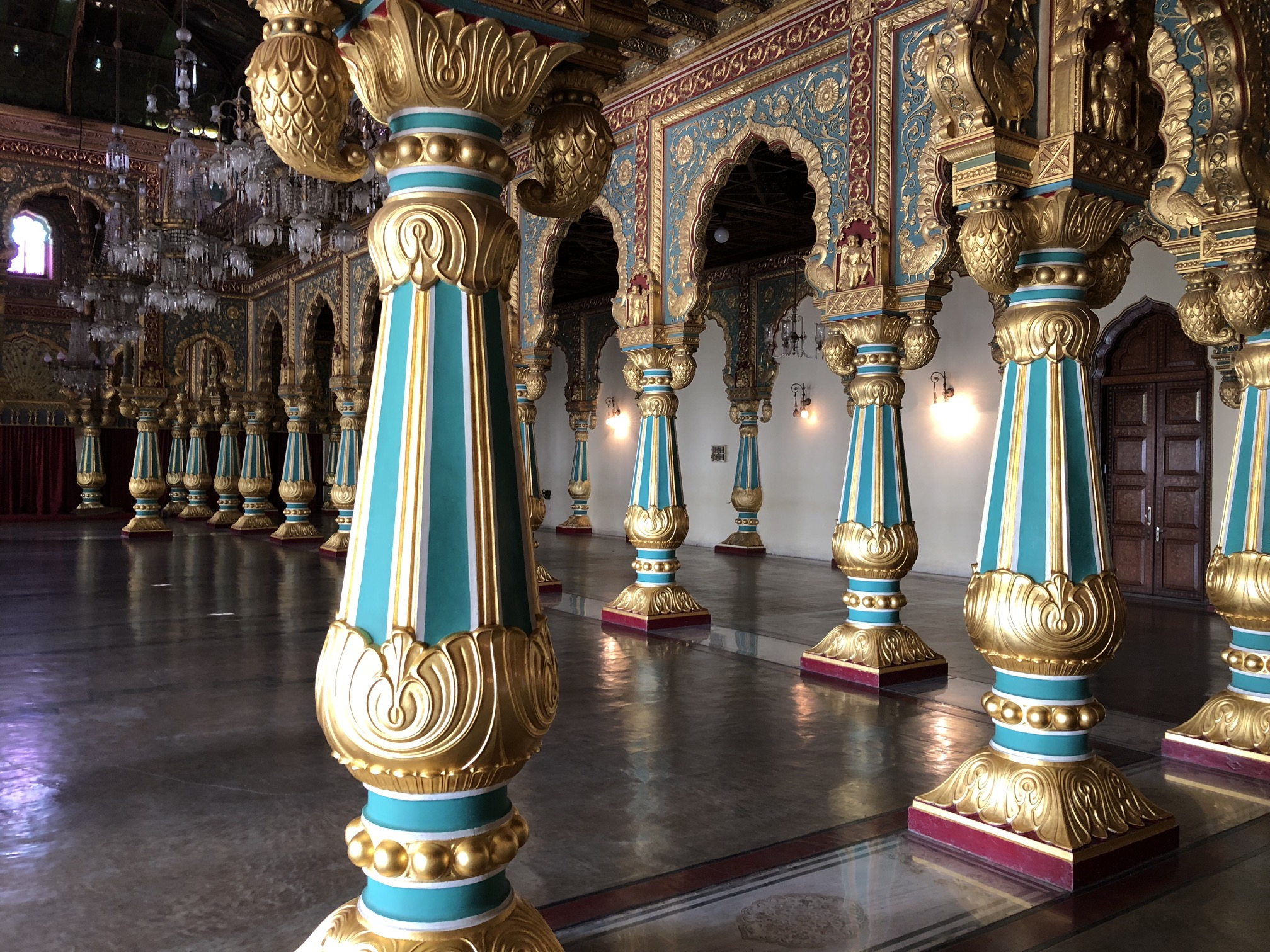 Columns of aqua and gold support a high ceiling with chandoliers.