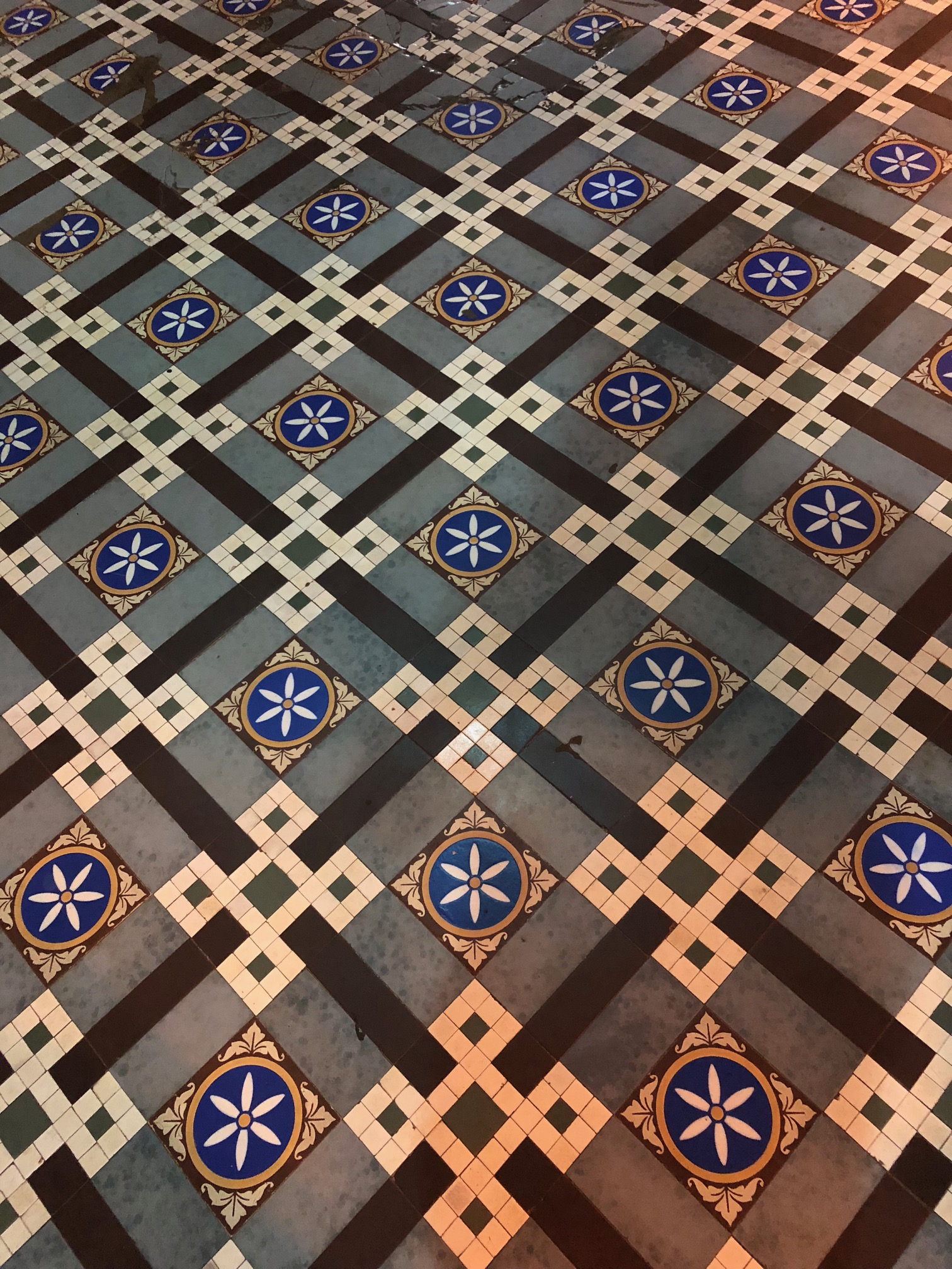 An intricate square pattern of floor tiles, including white six-petaled flowers on a blue background and small off-white tiles arranged in a heraldic knot.