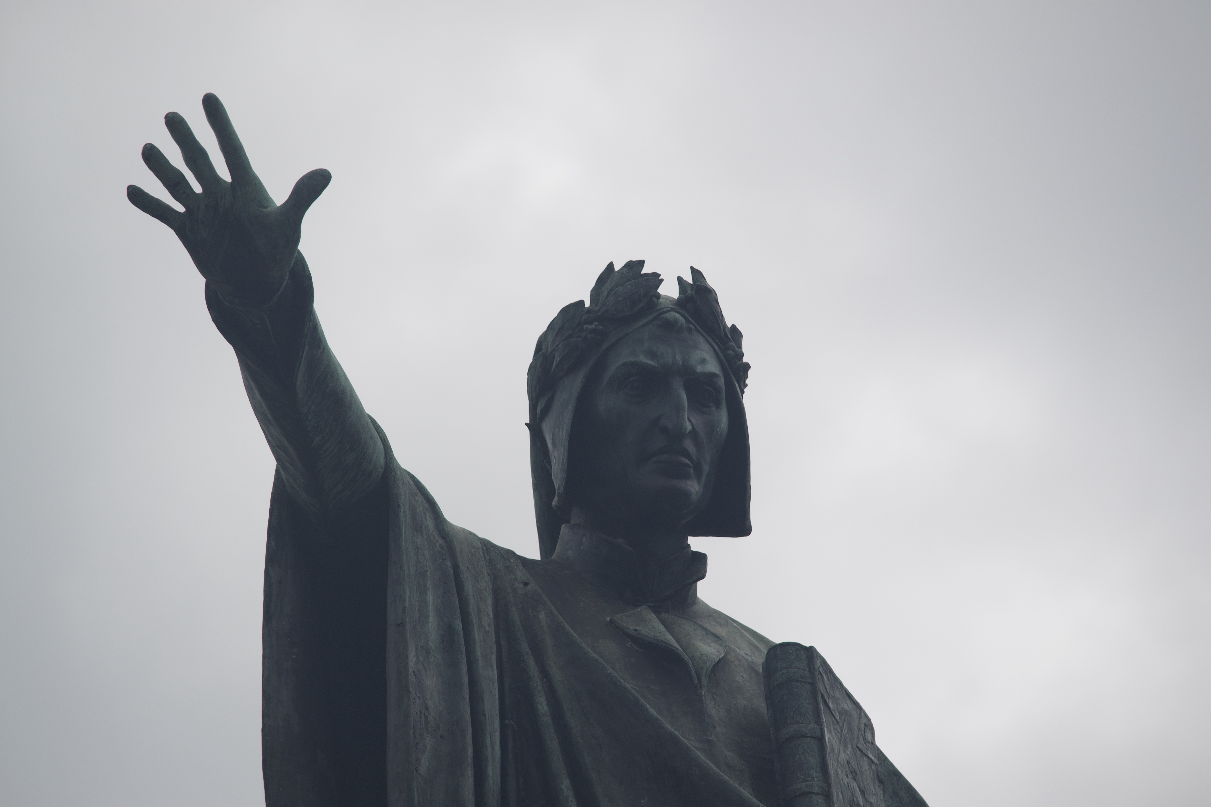A statue of a serious man with a laurel crown extending his right hand, fingers spread.