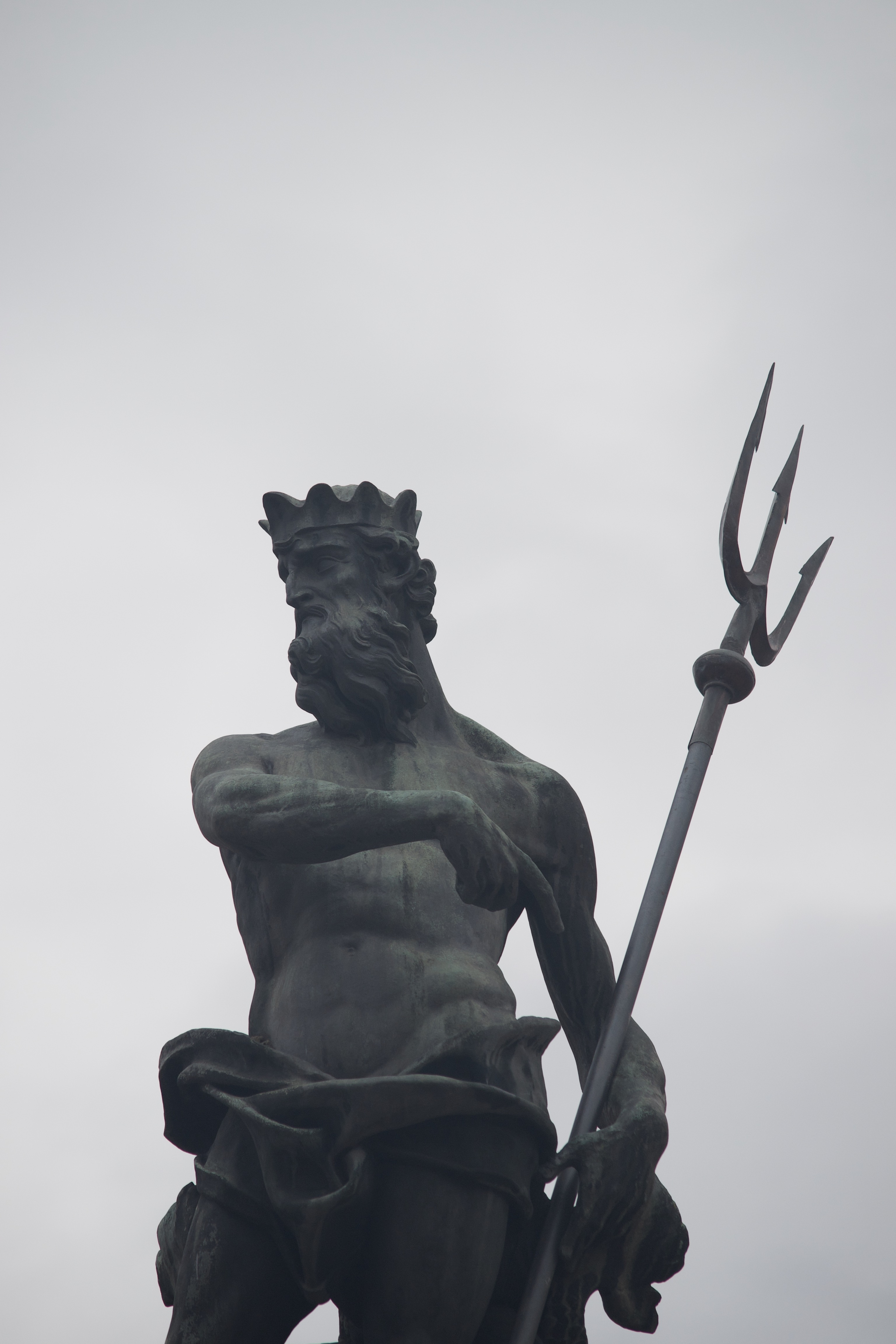 A shirtless, crowned, metal figure points with his right hand to the trident held by his left.