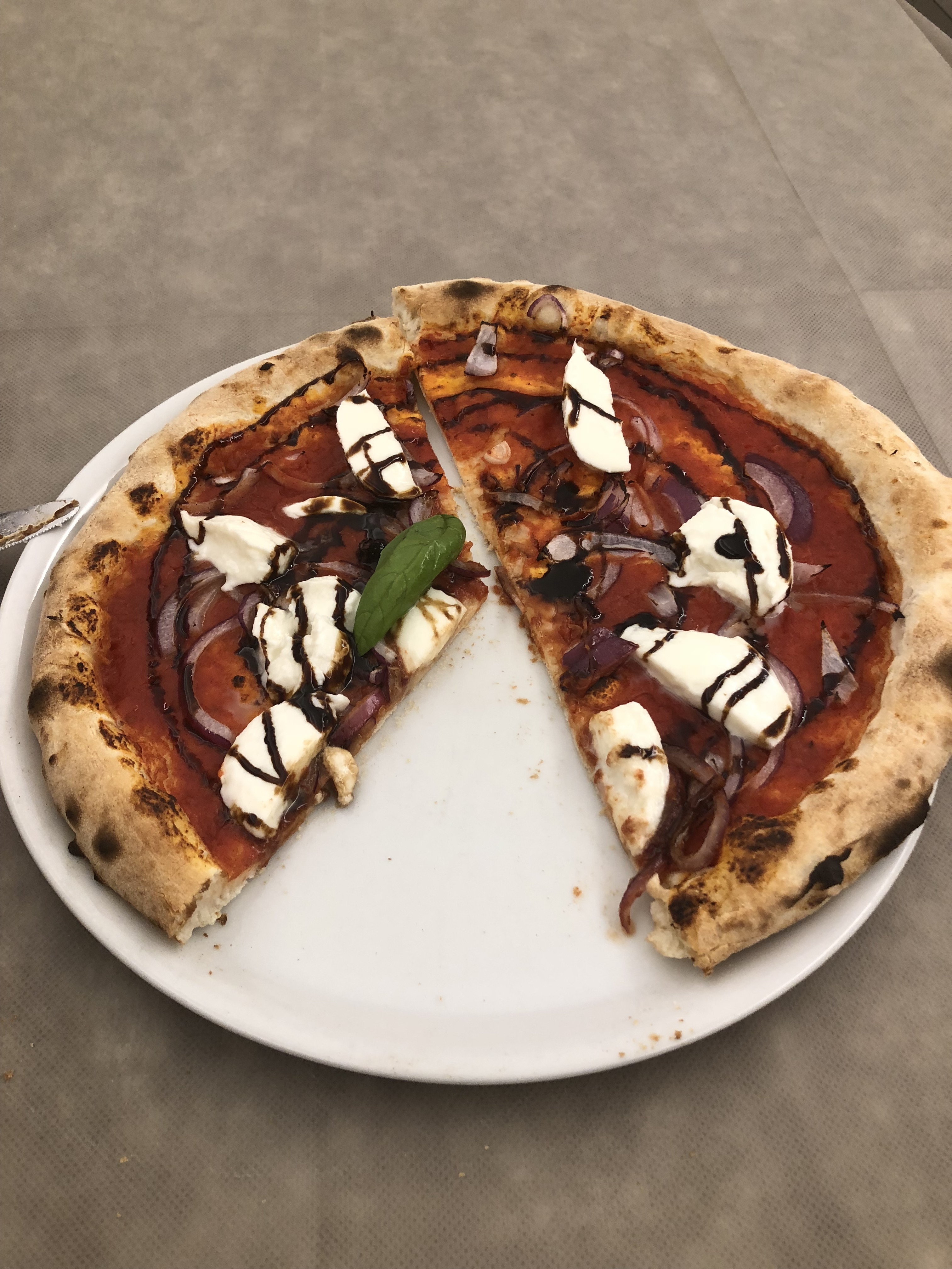 A pizza with fresh mozzarella drizzled with a reduced balsamic vinegar.  One slice is missing.